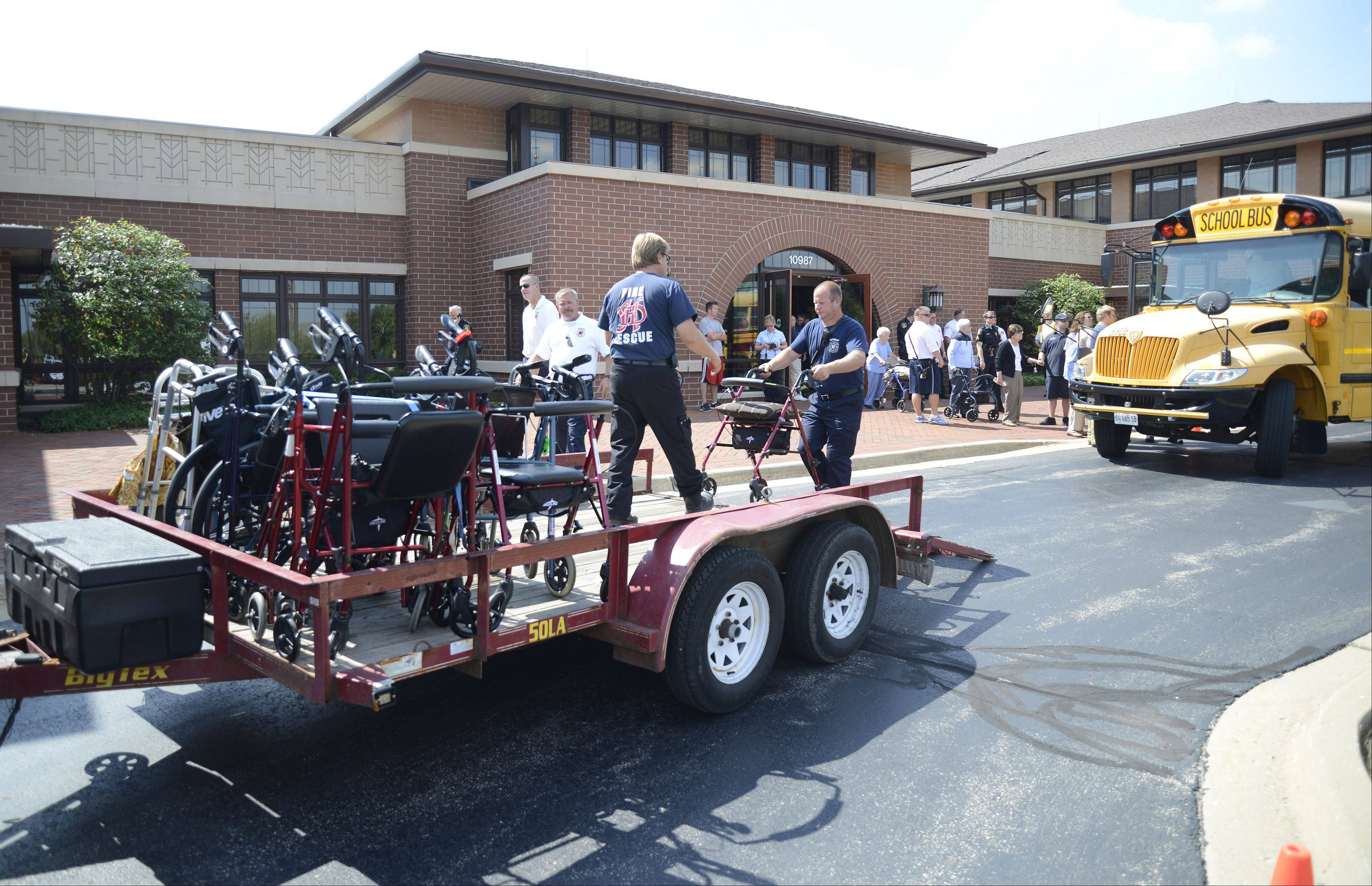 Huntley fire department mechanic, Rob Territo takes a walker from Huntley firefighter/paramedic Eric Smith to load onto a flatbed as residents get onto a bus to be taken home after a gas leak forced their evacuation from supportive and assisted living facilities in Huntley.