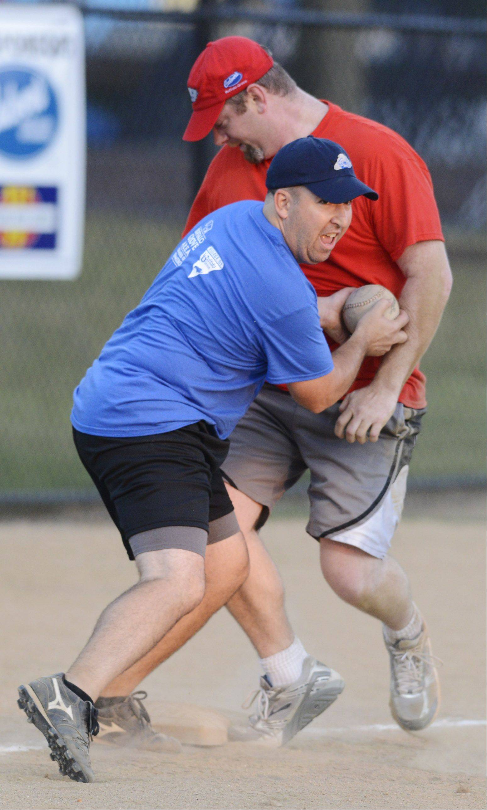 JOE LEWNARD/jlewnard@dailyherald.comGreg Ney, superintendent of recreation for the Buffalo Grove Park District, applies a late tag to Aaron Rochholz of PNC Bank at third base during Wednesday's annual charity softball game at Emmerich Park in Buffalo Grove.