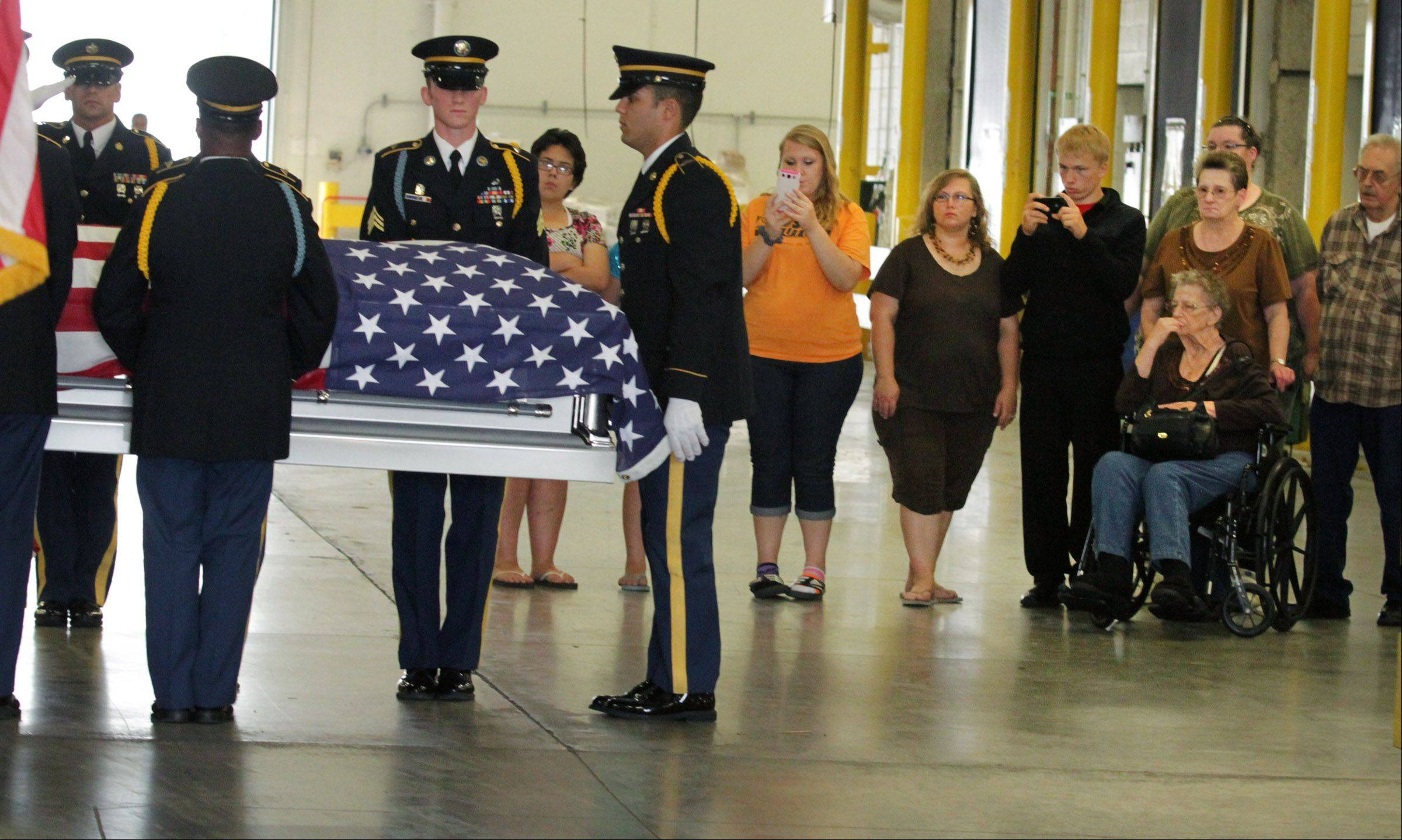 Donna Mitchell, 80, seated at right, and her daughter Donna Keefer behind her, watch as the coffin of Mitchell's twin brother, Army Cpl. Donald V. MacLean, is carried to a hearse by an Army honor guard Wednesday at O'Hare International Airport.