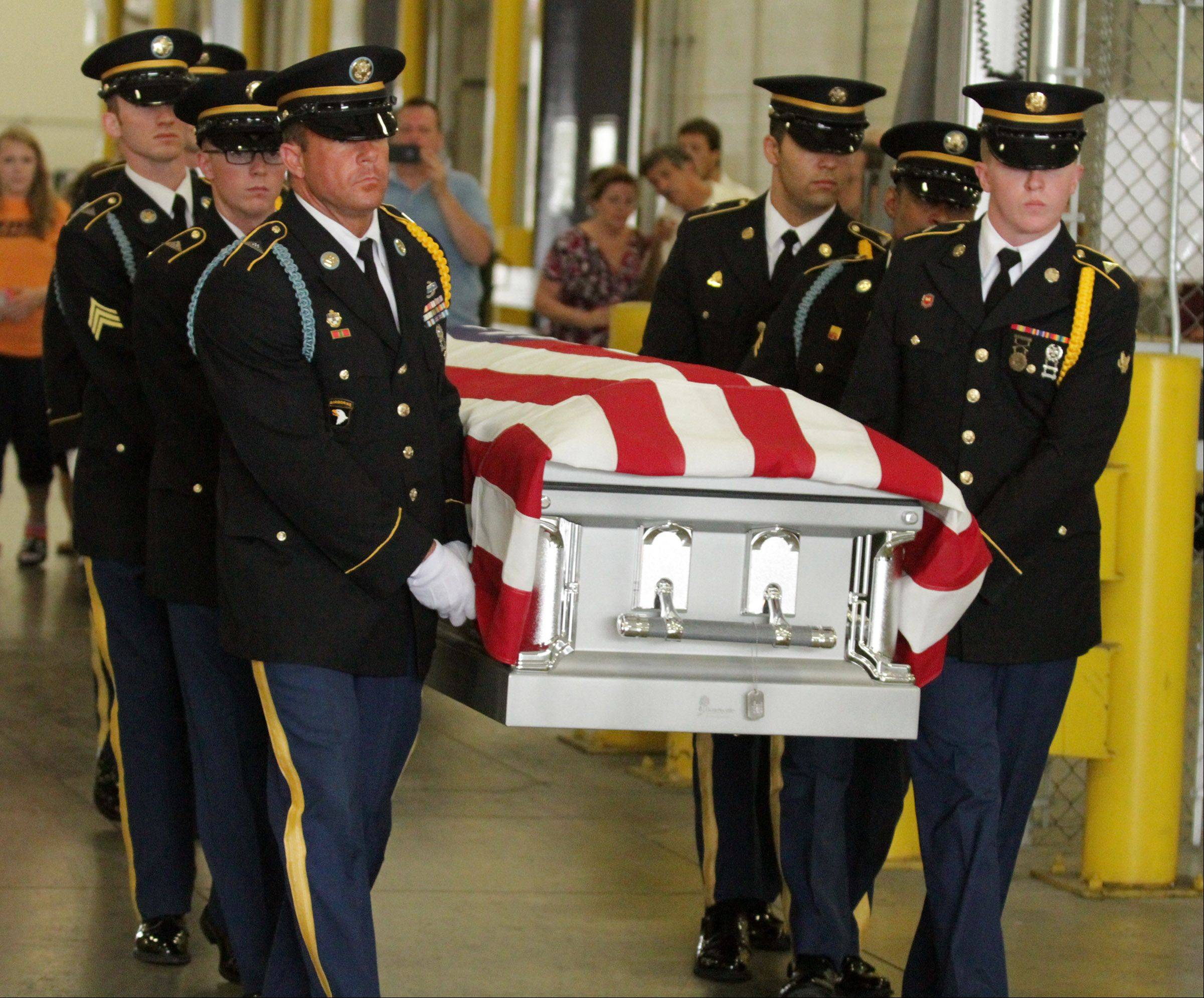 In a silver casket draped in a U.S. flag and carried by an Army honor guard, the remains of Army Cpl. Donald V. MacLean arrive Wednesday at O'Hare International Airport. New testing identified the remains 63 years after the 17-year-old soldier was killed during the Battle of Chosin Reservoir in Korea.