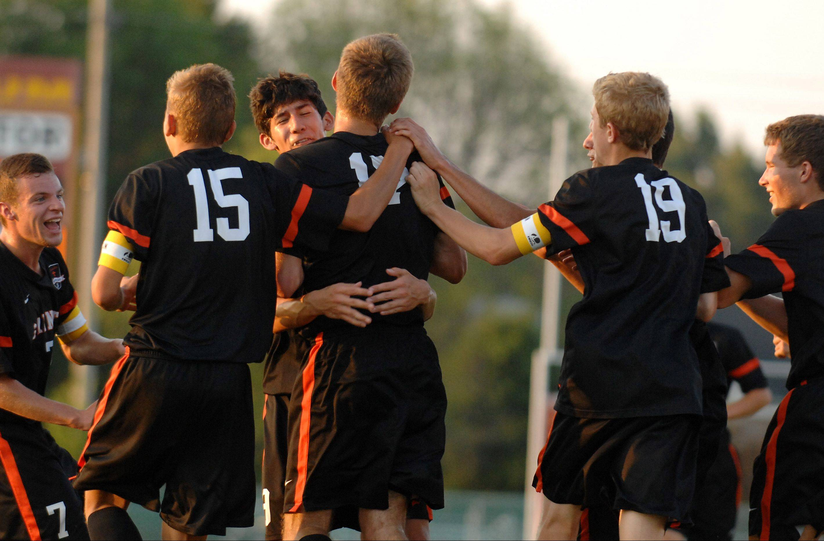 Teammates swarm St. Charles East's Evan DiLeonardi, 17, after he scored the first goal for the Saints during Thursday's game in Batavia.