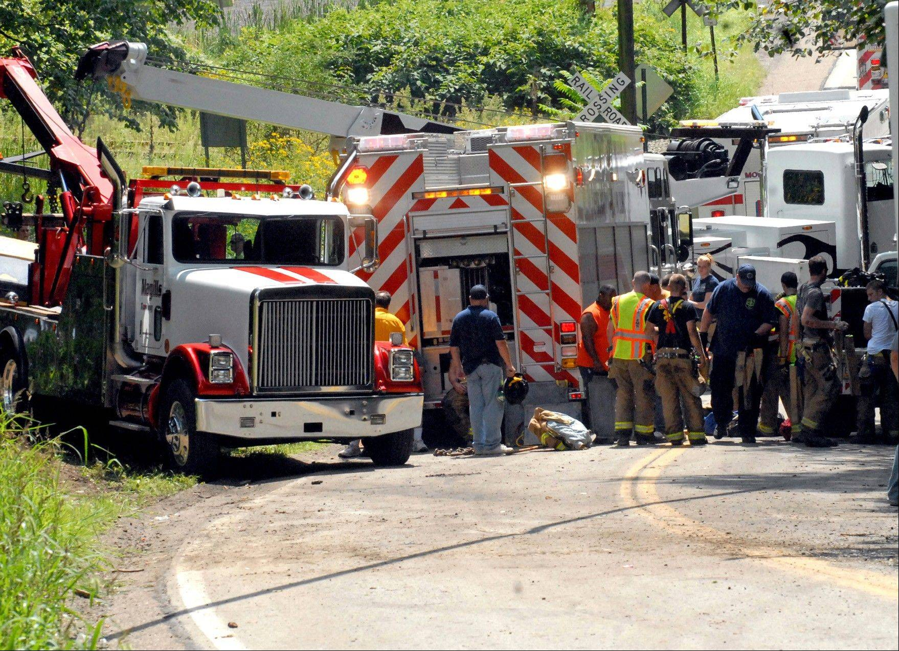 Emergency crews respond Friday to a man trapped under an asphalt steam roller truck on Saunders Station Road in Monroeville, Pa.
