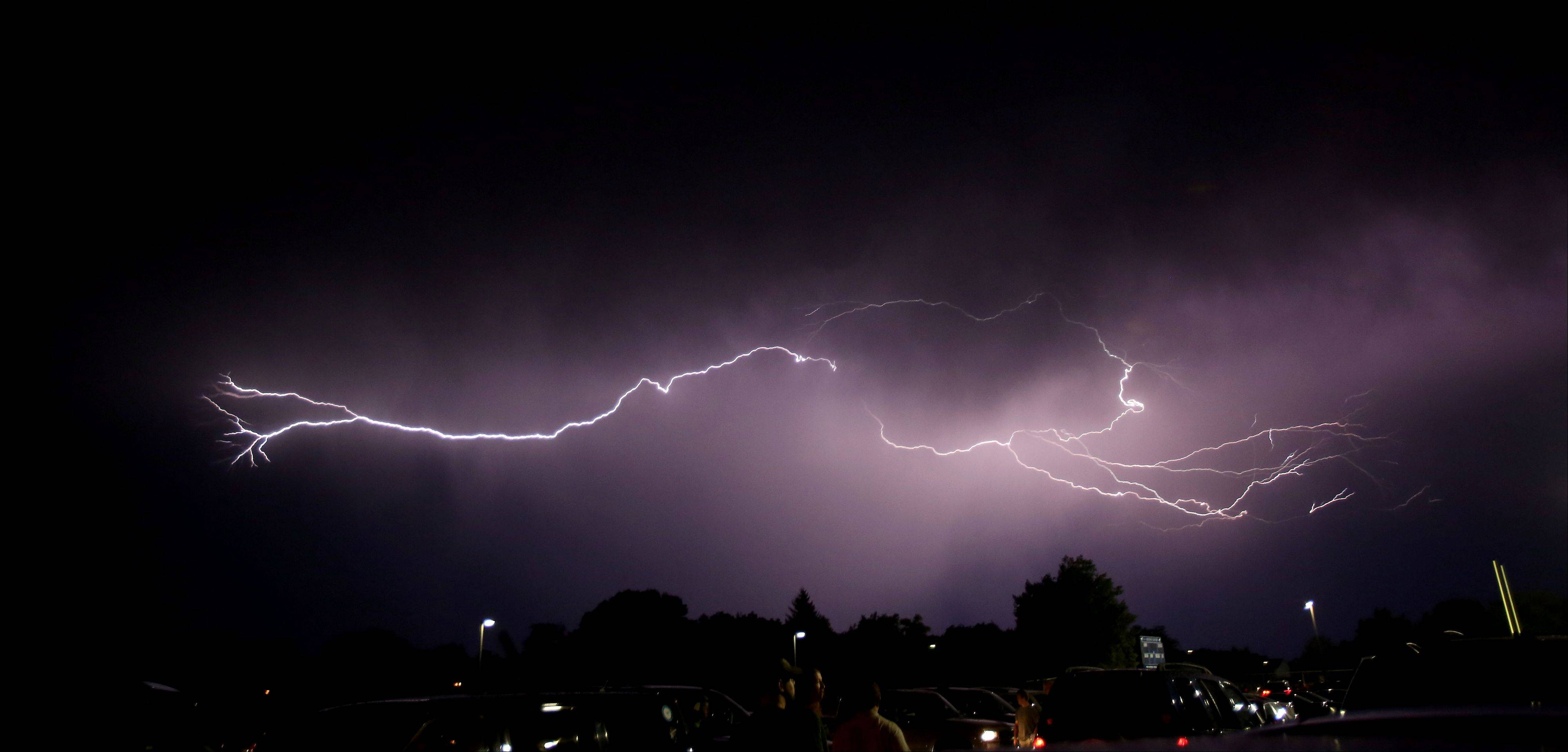Bev Horne/bhorne@dailyherald.com Streaks of lightning across the sky over the parking lot at Downers Grove South Friday night, where the football game against Benet had to be postponed until Saturday.