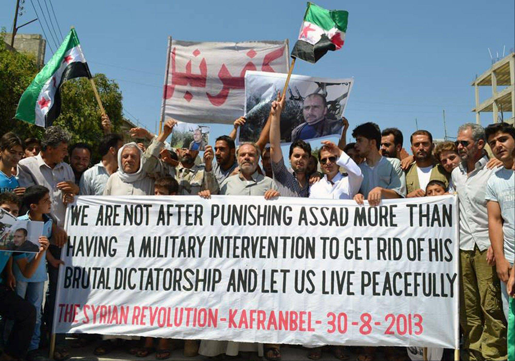Anti-Syrian regime protesters holding a banner and Syrian revolution flags, during a demonstration in Kafr Nabil town, in Idlib province, northern Syria, Friday, Aug. 30, 2013. United Nations experts are investigating the alleged use of chemical weapons in Syria as the United States and its allies prepare for the possibility of a punitive strike against President Bashar Assad's regime, blamed by the Syrian opposition for the attack.