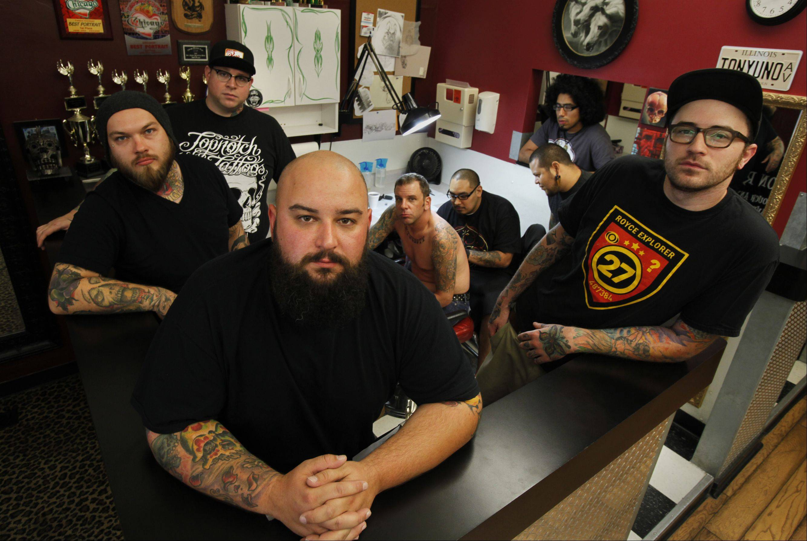 Luke Clifford, front, and his 216 E. Crew at Topnotch Tattoos in Elgin, which opened in 1999. Two other tattoo shops are hoping to open nearby in downtown Elgin.