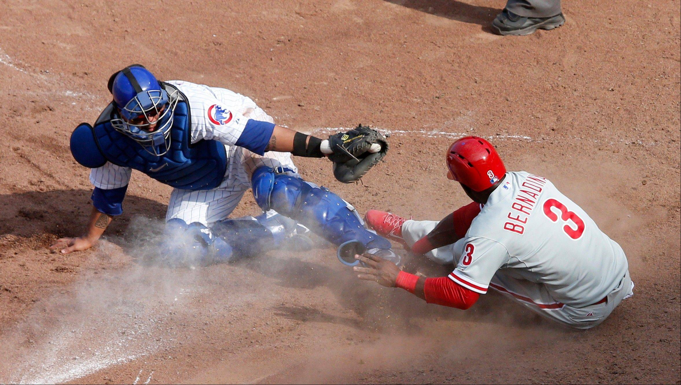 The Phillies' Roger Bernadina scores past Cubs catcher Dioner Navarro on a single by Michael Young during the ninth inning Friday in Chicago.