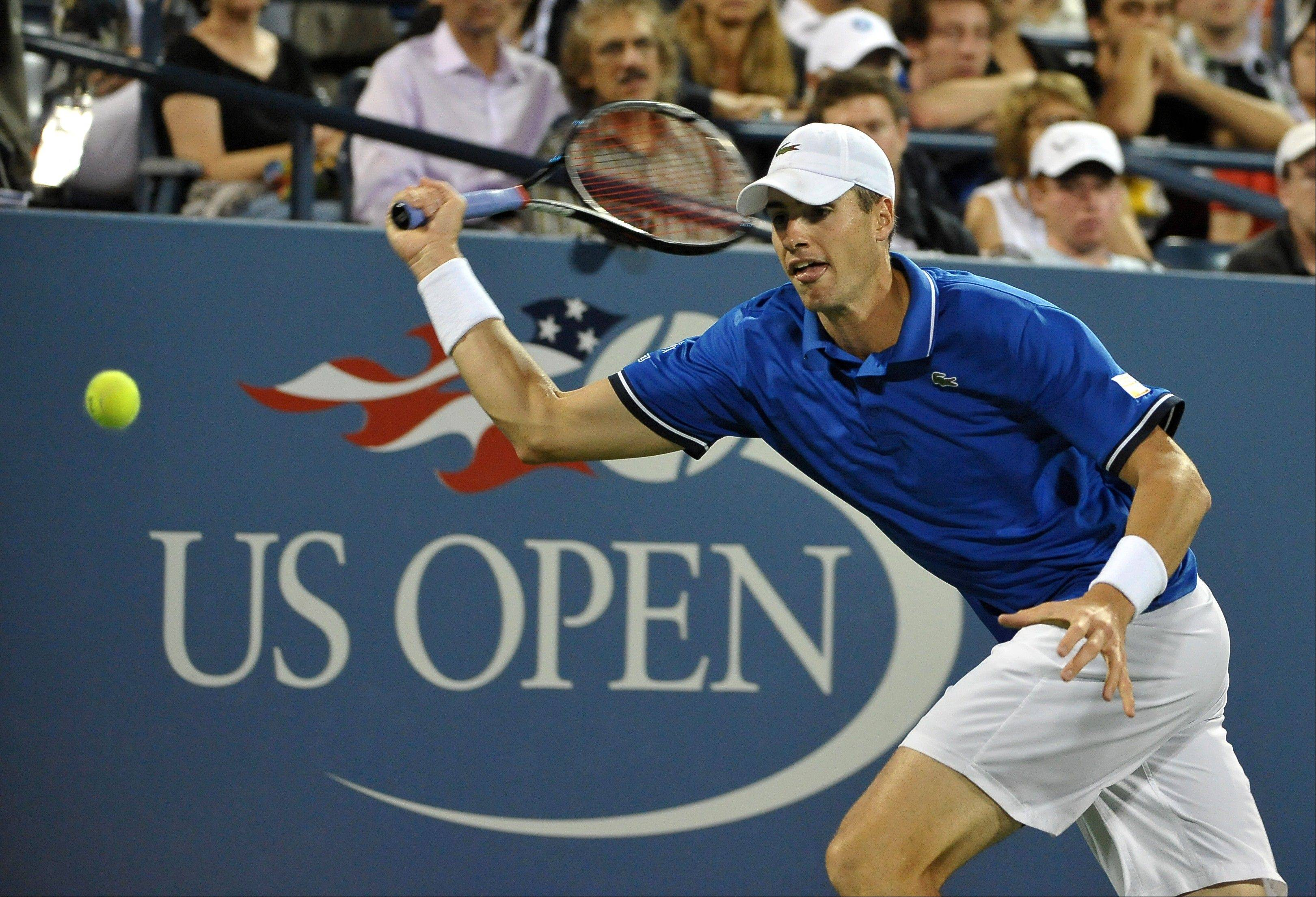John Isner runs for the ball against Gael Monfils at the U.S. Open on Thursday in New York.