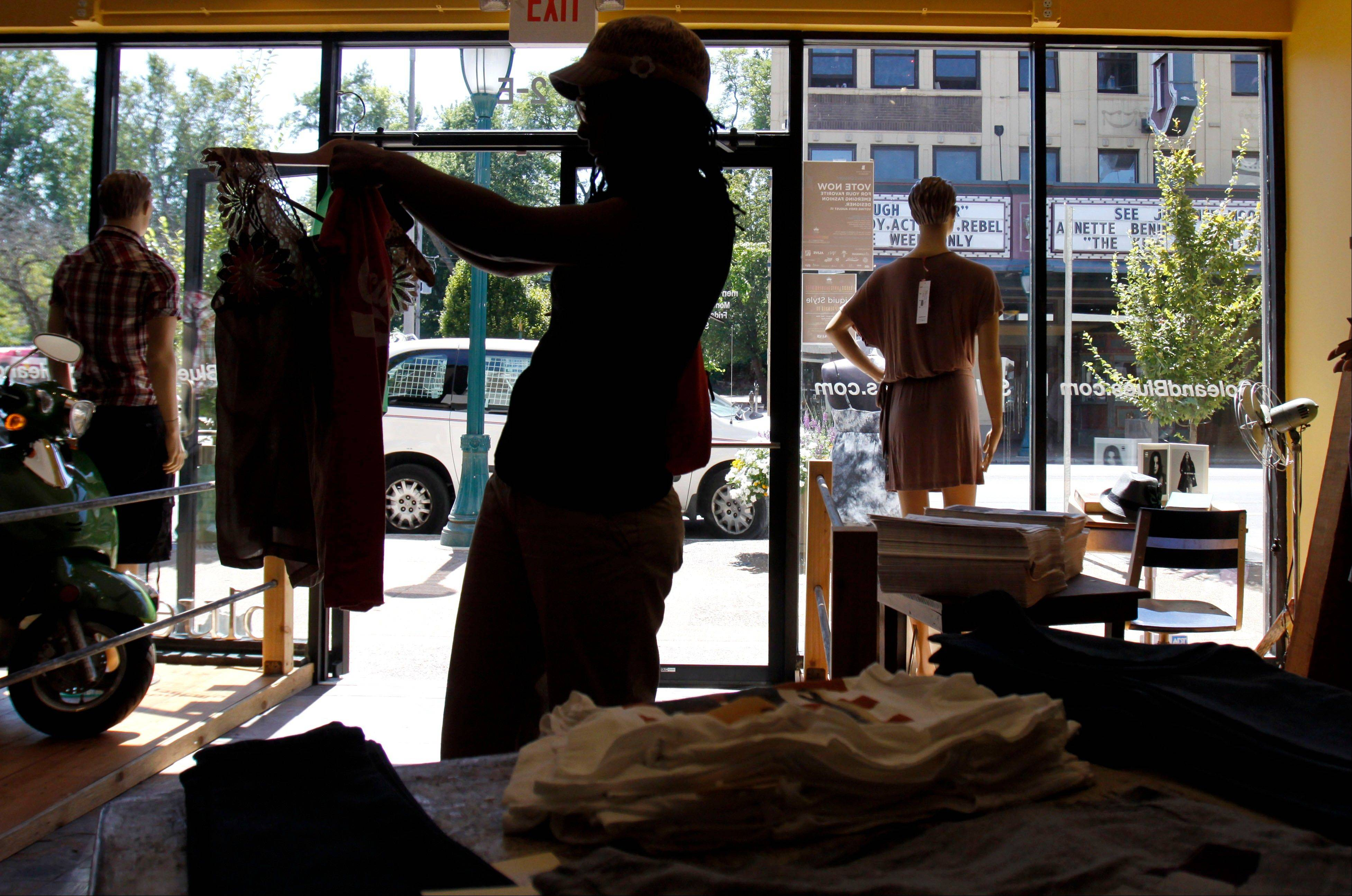 Kim Miller shops for clothes in St. Louis. The Commerce Department said Friday that consumer spending rose just 0.1 percent in July from the previous month.
