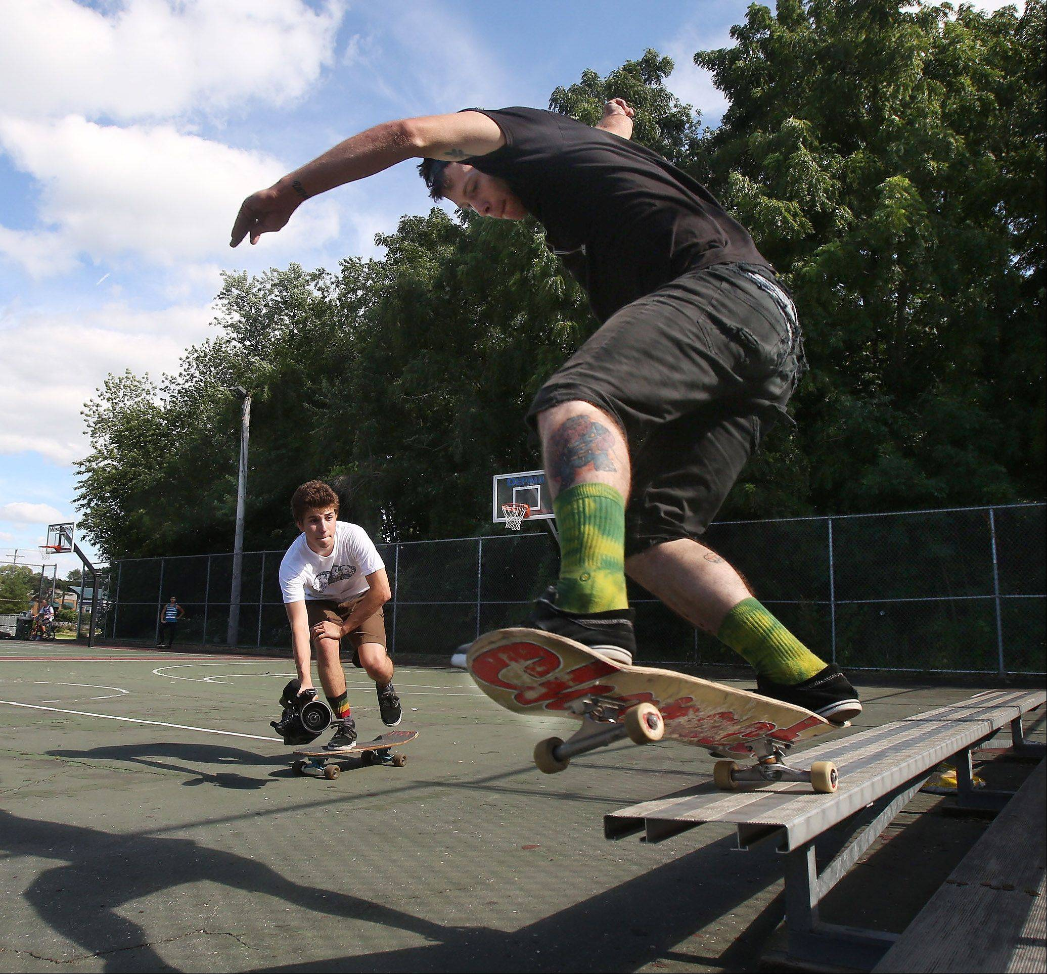 Max Kollman shoots video of street skateboarder Scotty Brooke of McHenry on an outdoor basketball court in McHenry.