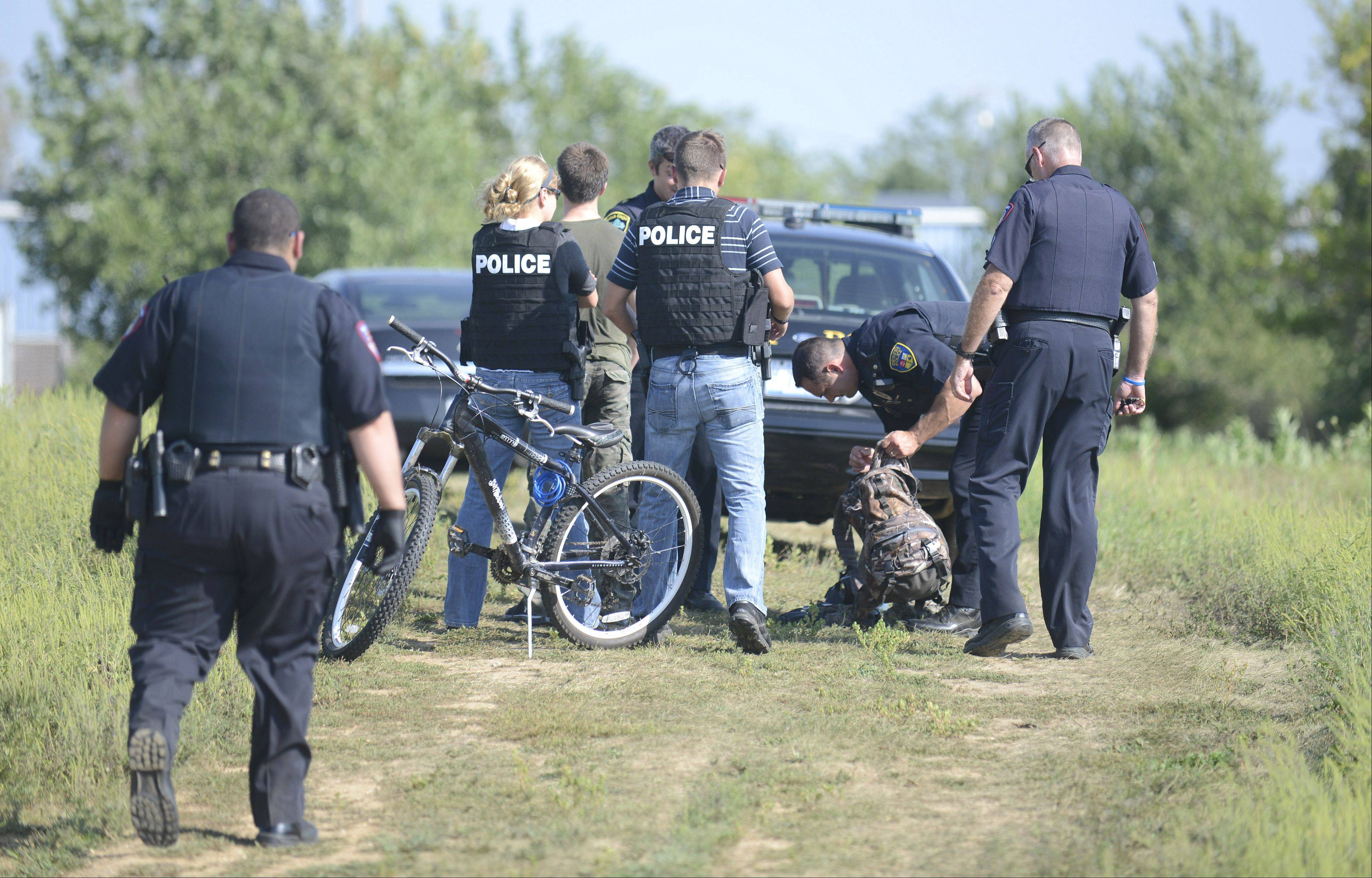 Kane County Sheriff's Department officers check the contents of a backpack Friday near Kaneland John Stewart Elementary School in Elburn after three 13-year-old boys were taken into custody following reports of suspicious activity near the school.