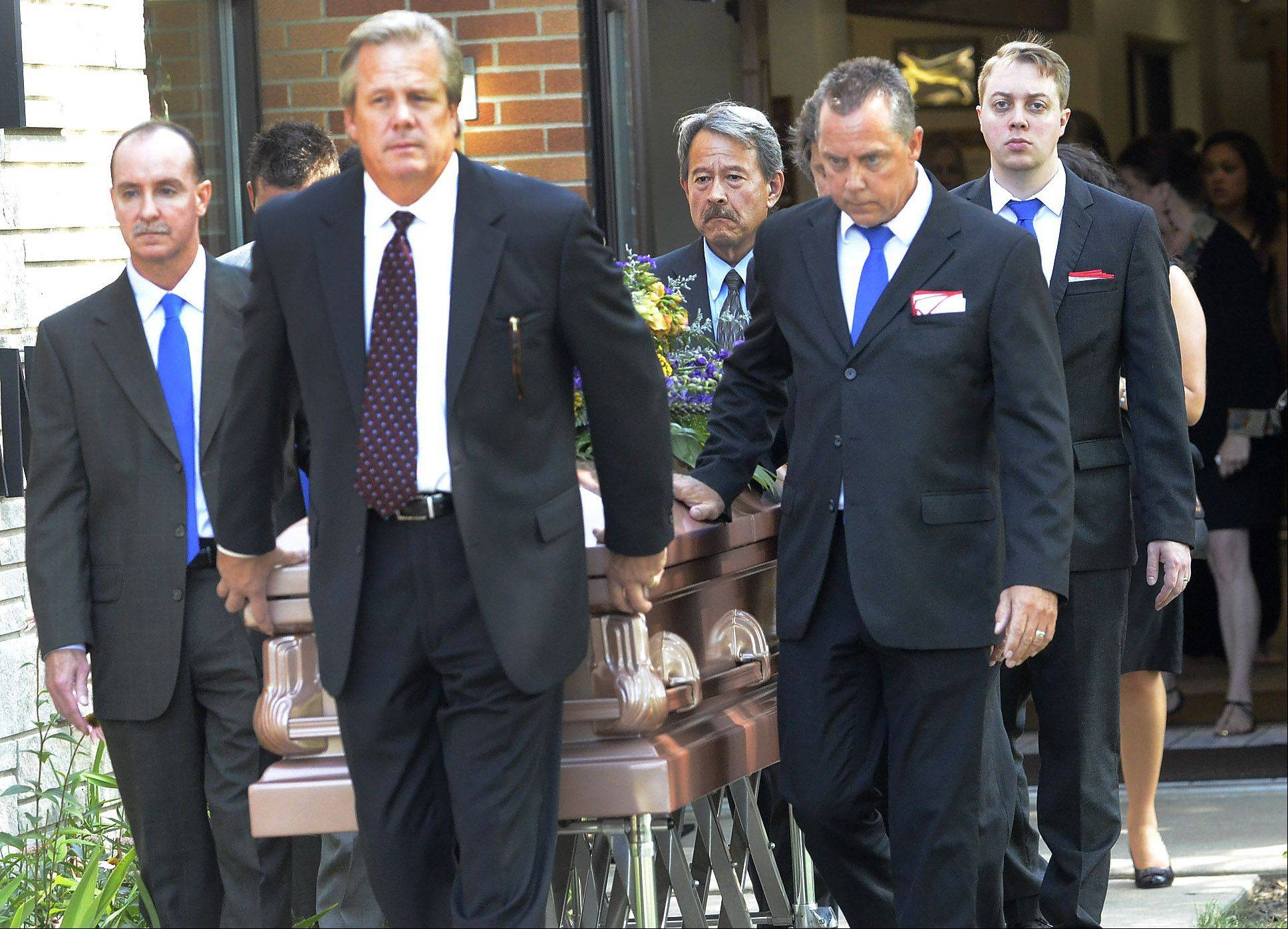 Pallbearers wear Cubs blue ties honoring longtime Mundelein resident and Kirk Players founder John Lynn, during his funeral.
