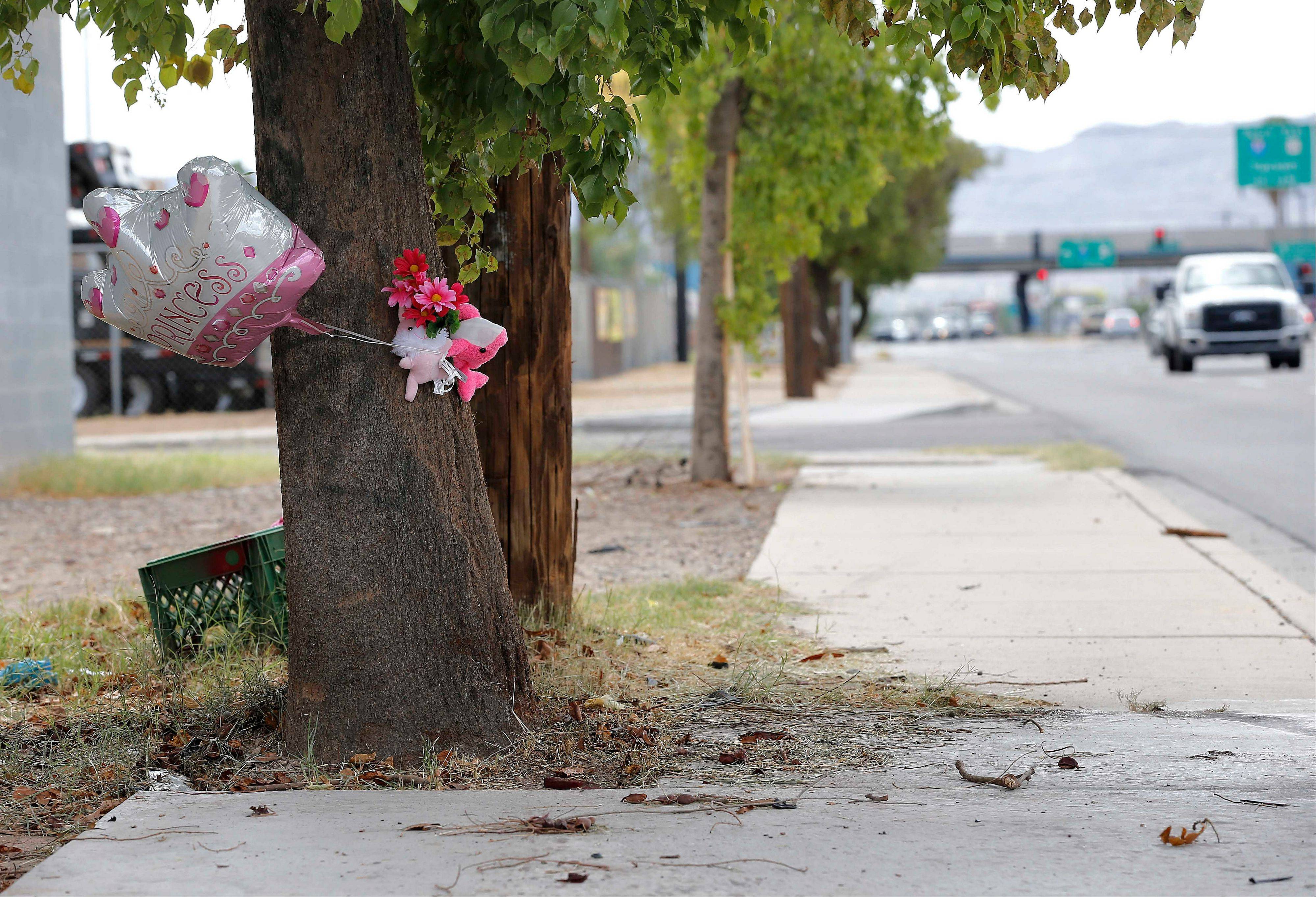 A makeshift memorial on a tree is shown, Thursday, Aug. 29, 2013, in Phoenix. An 8-year-old boy was driving his mother's car on a nighttime joy ride with his 6-year-old sister when it crashed into a telephone pole, behind the tree, fatally injuring the girl, police said Thursday.