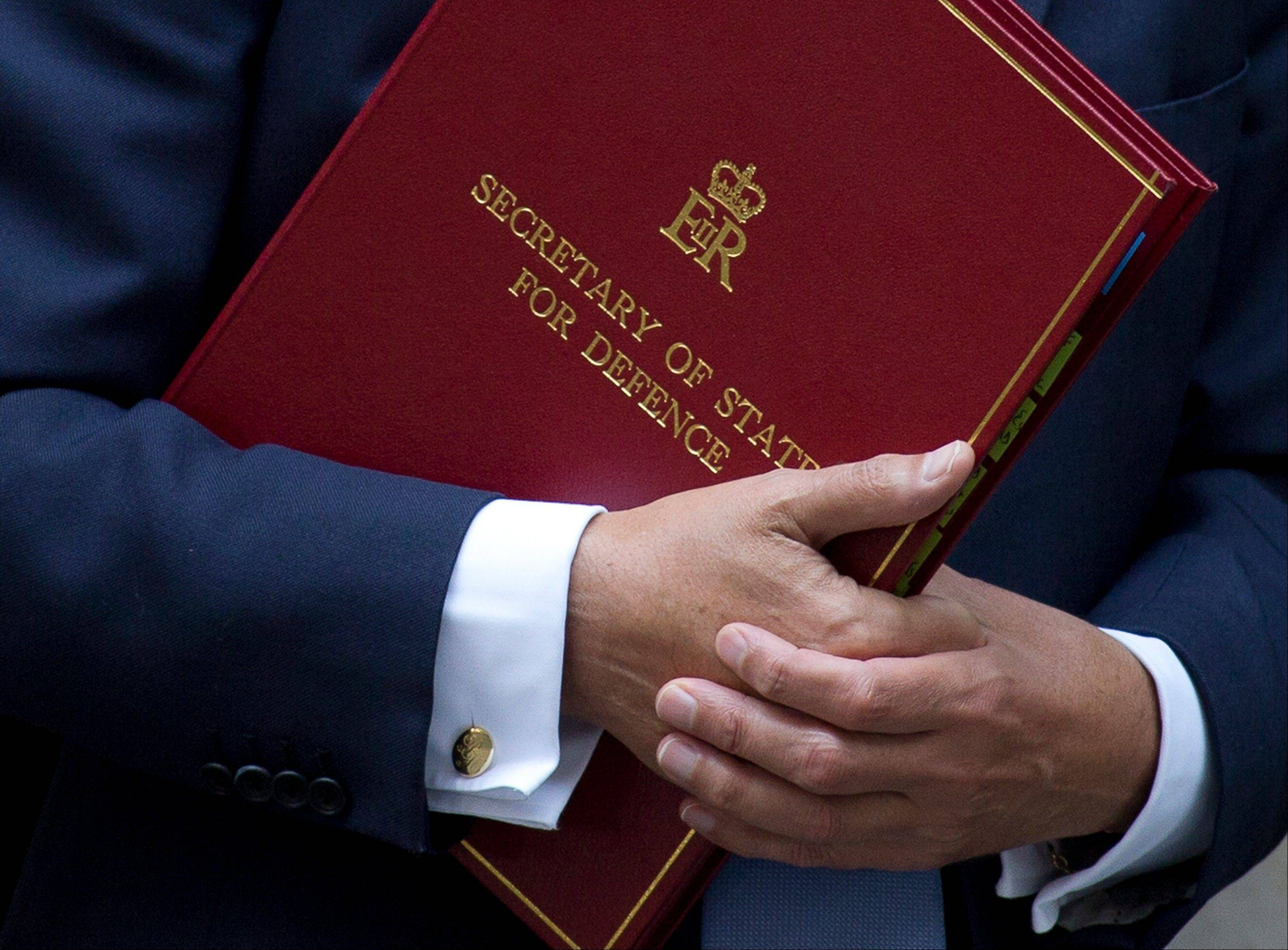 Britain's Defense Secretary Philip Hammond holds his traditional red ministerial folder as he leaves 10 Downing Street after a national security meeting at in London, Wednesday, Aug. 28, 2013. French President Francois Hollande expressed readiness Friday to push ahead with plans to strike Syria for allegedly using chemical weapons despite the British Parliament's rejection of military action.