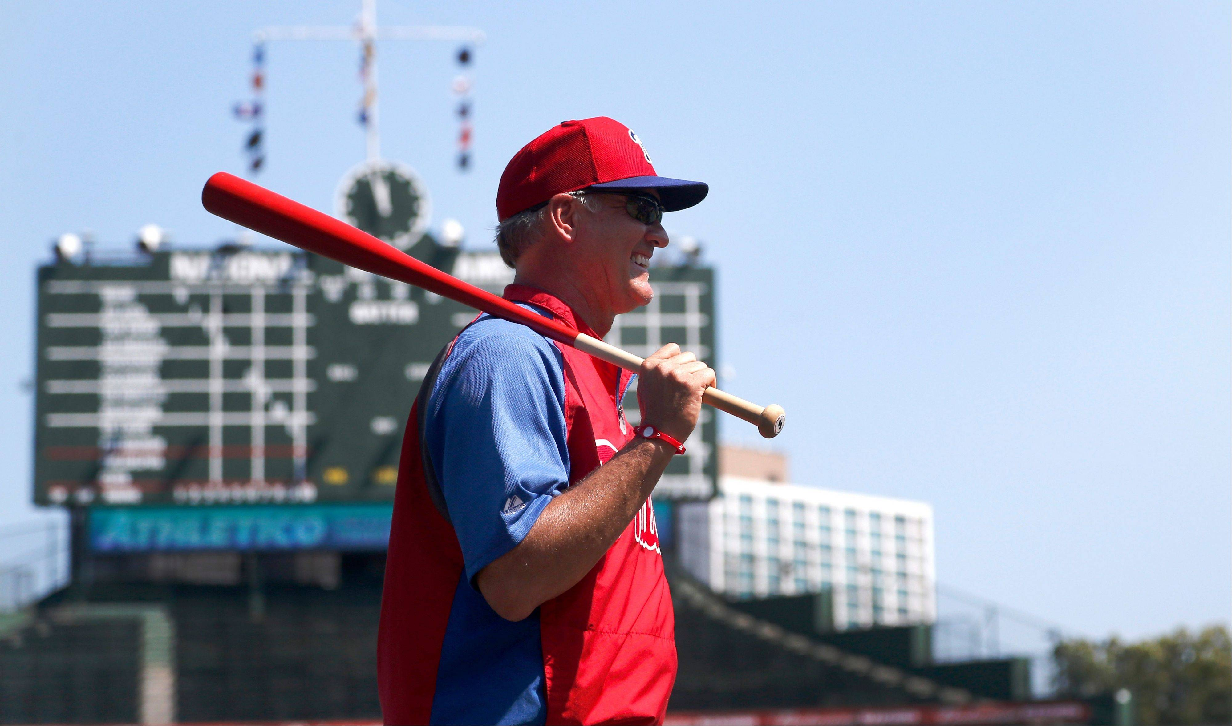 Phillies interim manager Ryne Sandberg looks out over field as he conducts infield practice before Friday's game at Wrigley Field.S