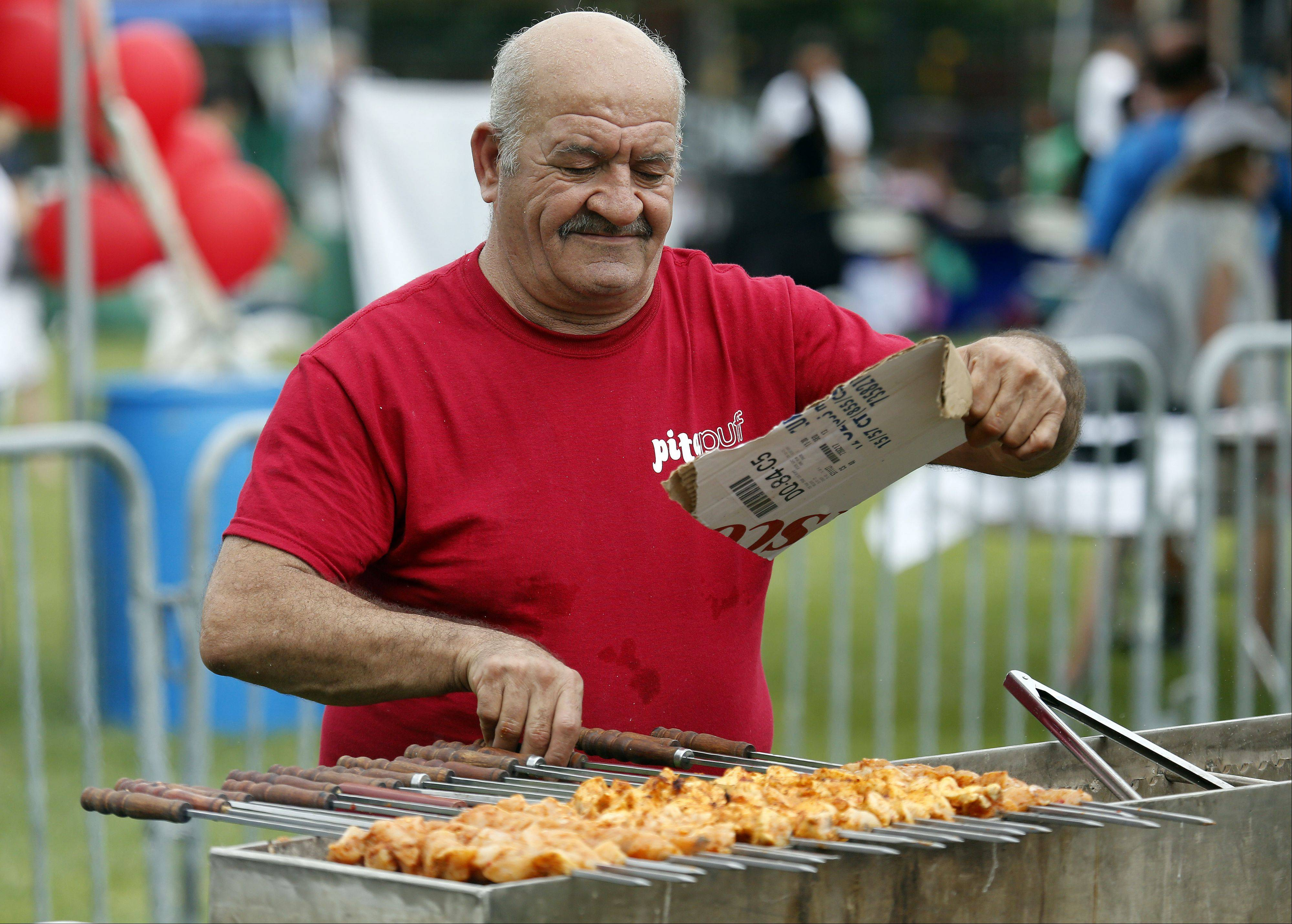 Joseph Shimon of Pita Puff Mediterranean Grill and Cafe works the grill as he cooks up some chicken kebabs Saturday during the Elgin International Festival at Festival Park.
