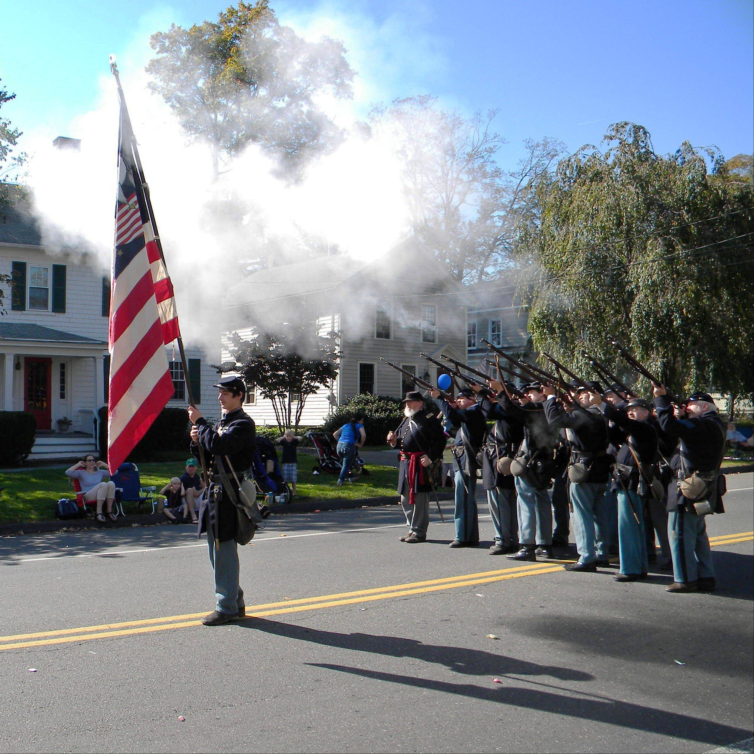 Civil War re-enactors fire a salute as spectators cover their ears during the Labor Day parade in Newtown, Conn. The 11th Connecticut Volunteer Infantry, Company A will march again in the town�s annual parade, but with black armbands and rifles pointed downward, a gesture of mourning, according to a father of a member of the unit. �They had decided independently that they shouldn�t be firing,� Dan Cruson said, nearly nine months after shootings at Sandy Hook Elementary School left 26 dead, 20 of them children.