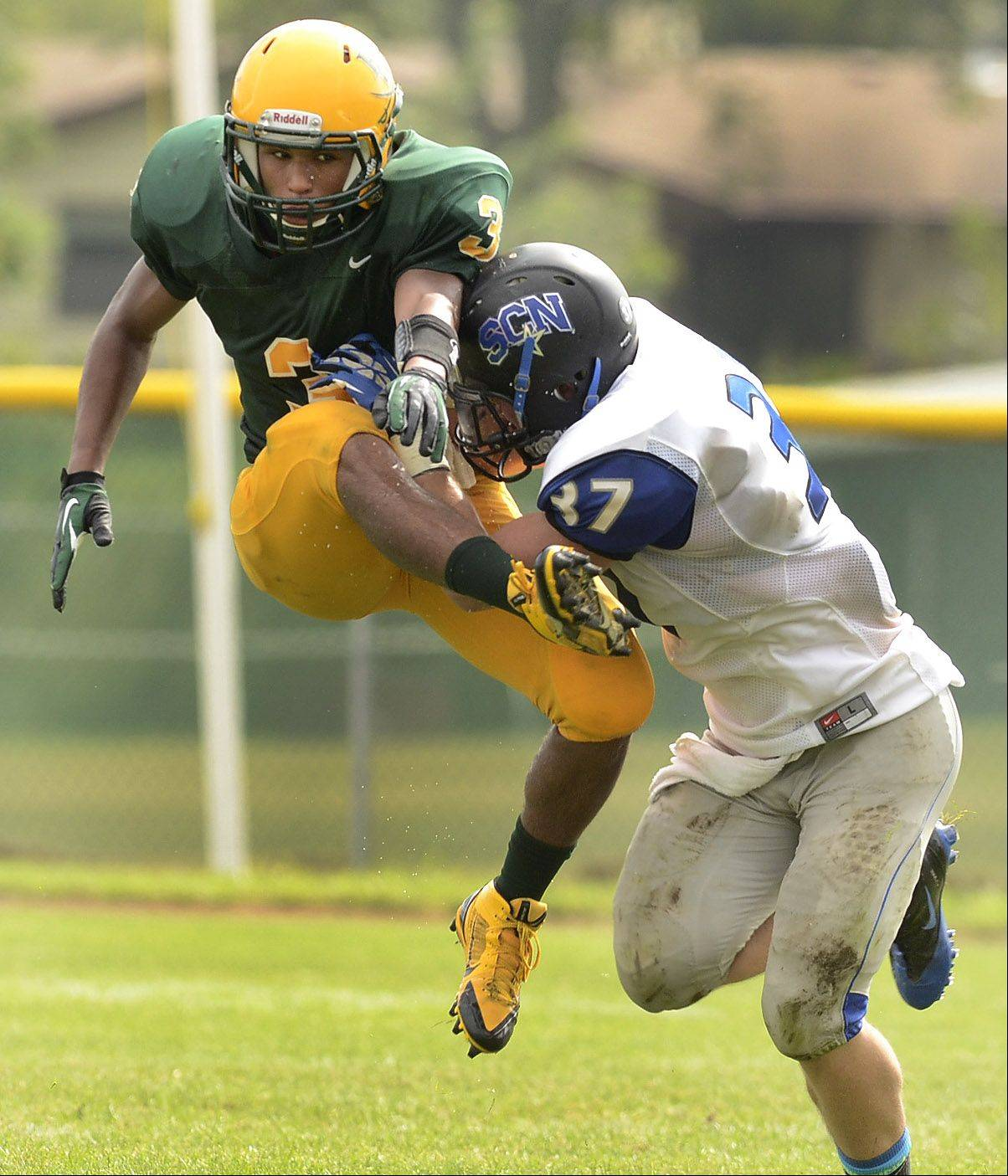 Elk Grove's Travon Royal just gets a kick away, narrowly avoiding a block by Reece Conroyd of St. Charles North.