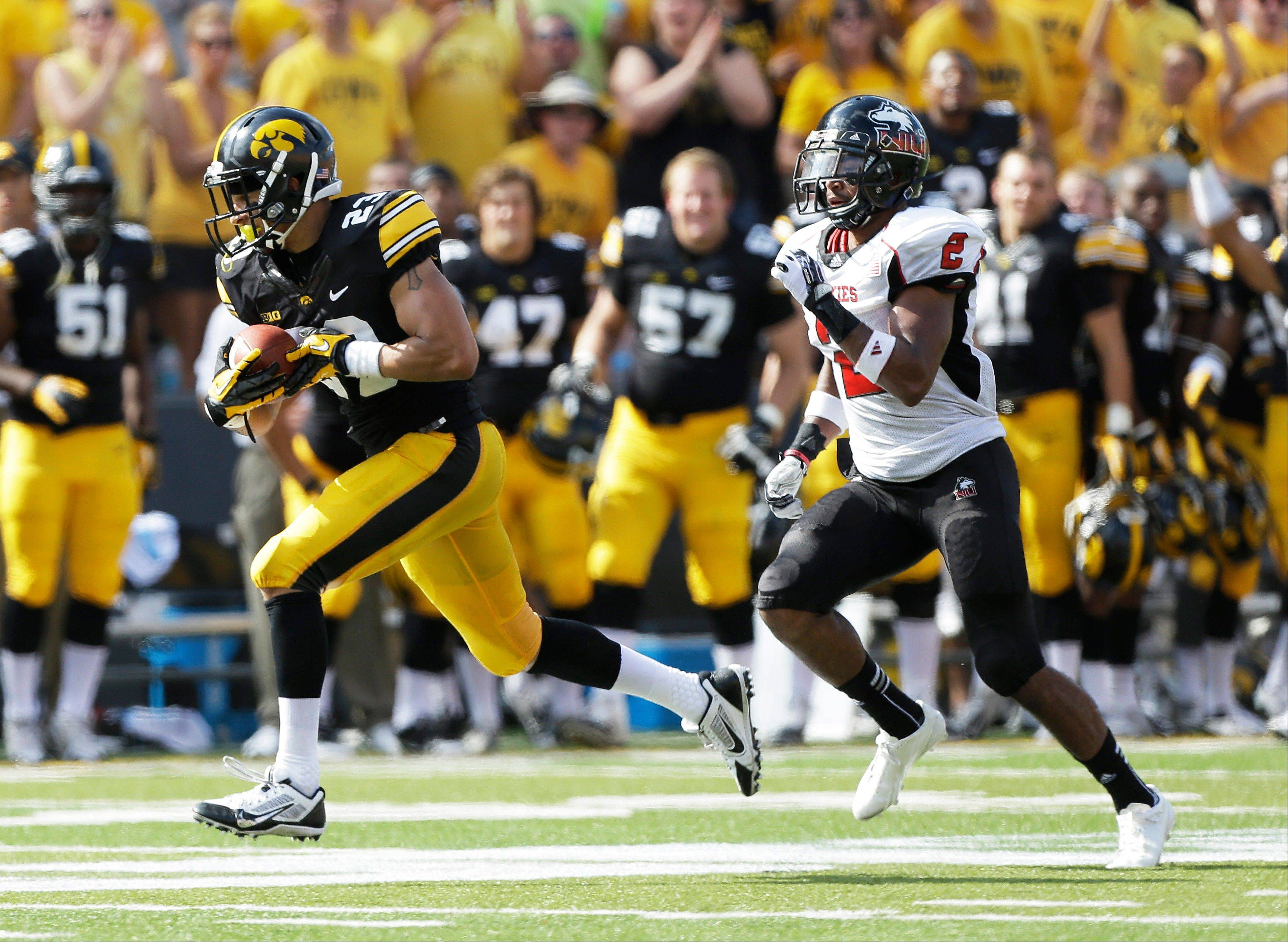 Iowa wide receiver Jordan Cotton, left, runs from Northern Illinois cornerback Sean Evans after catching a 53-yard pass during the first half of an NCAA college football game Saturday in Iowa City, Iowa.