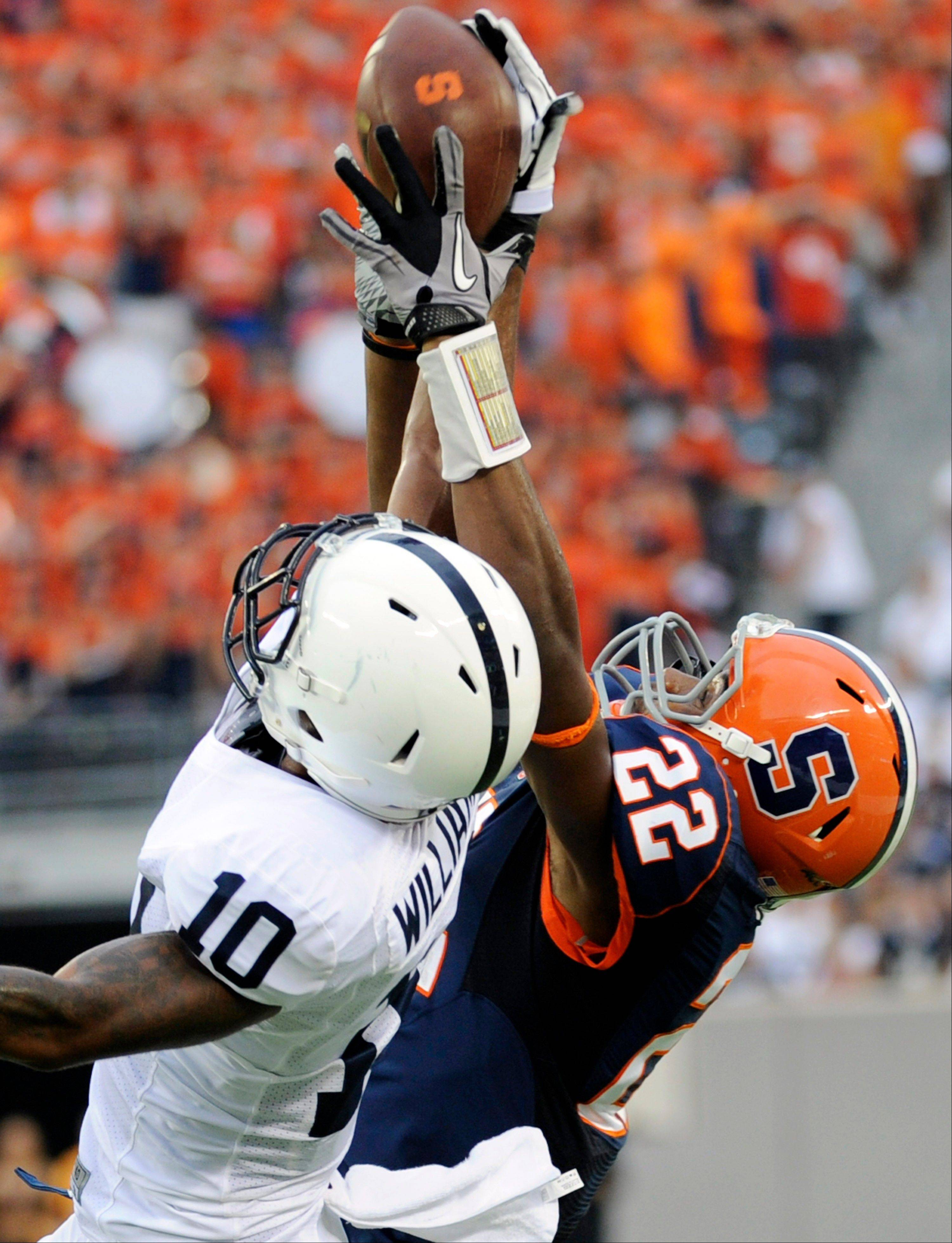 Syracuse wide receiver Adrian Flemming (22) makes a catch over Penn State cornerback Trevor Williams during the third quarter of an NCAA college football game Saturday in East Rutherford, N.J. Penn State won 23-17.
