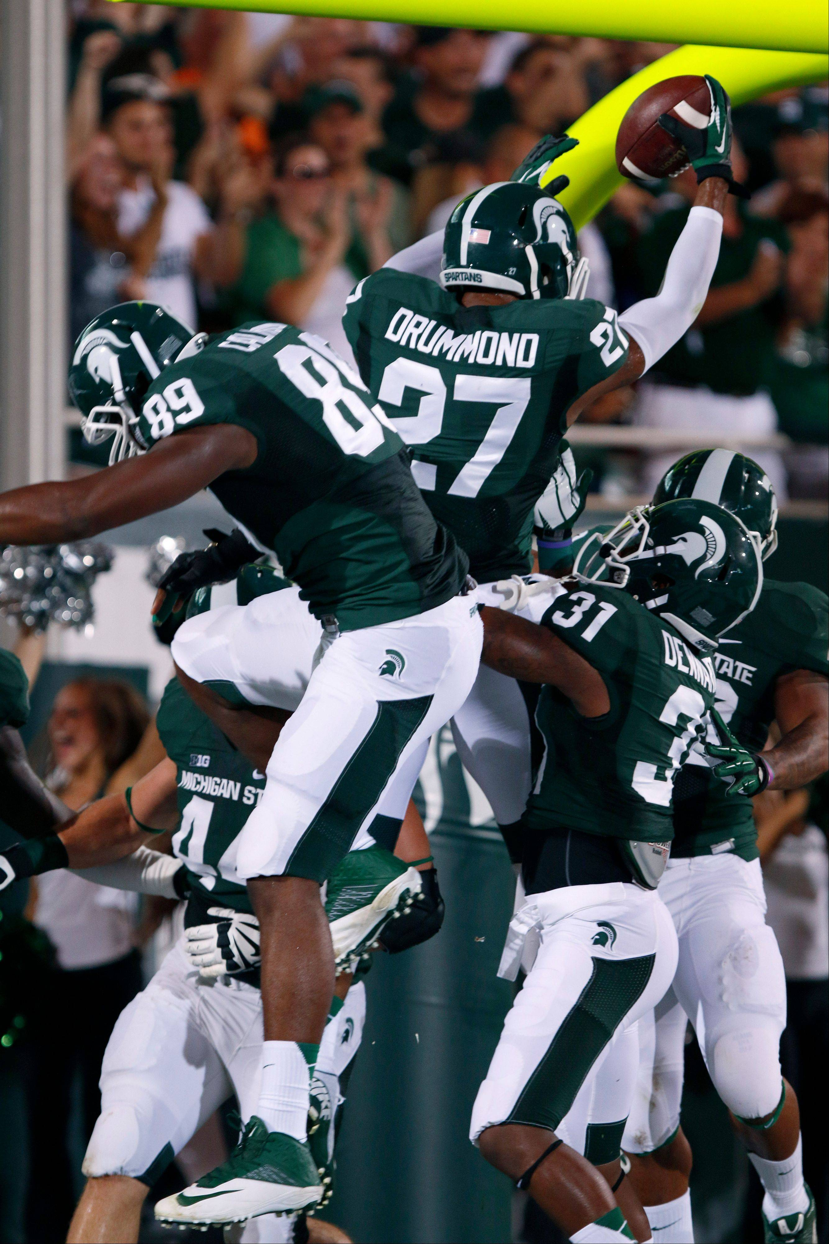 Michigan State�s Kurtis Drummond (27), Shilique Calhoun (89) and Darqueze Dennard (31) celebrate Drummond�s interception return for a touchdown during the first quarter against Western Michigan on Friday in East Lansing, Mich. The ball was intercepted by Jairus Jones and lateraled to Drummond for the score.