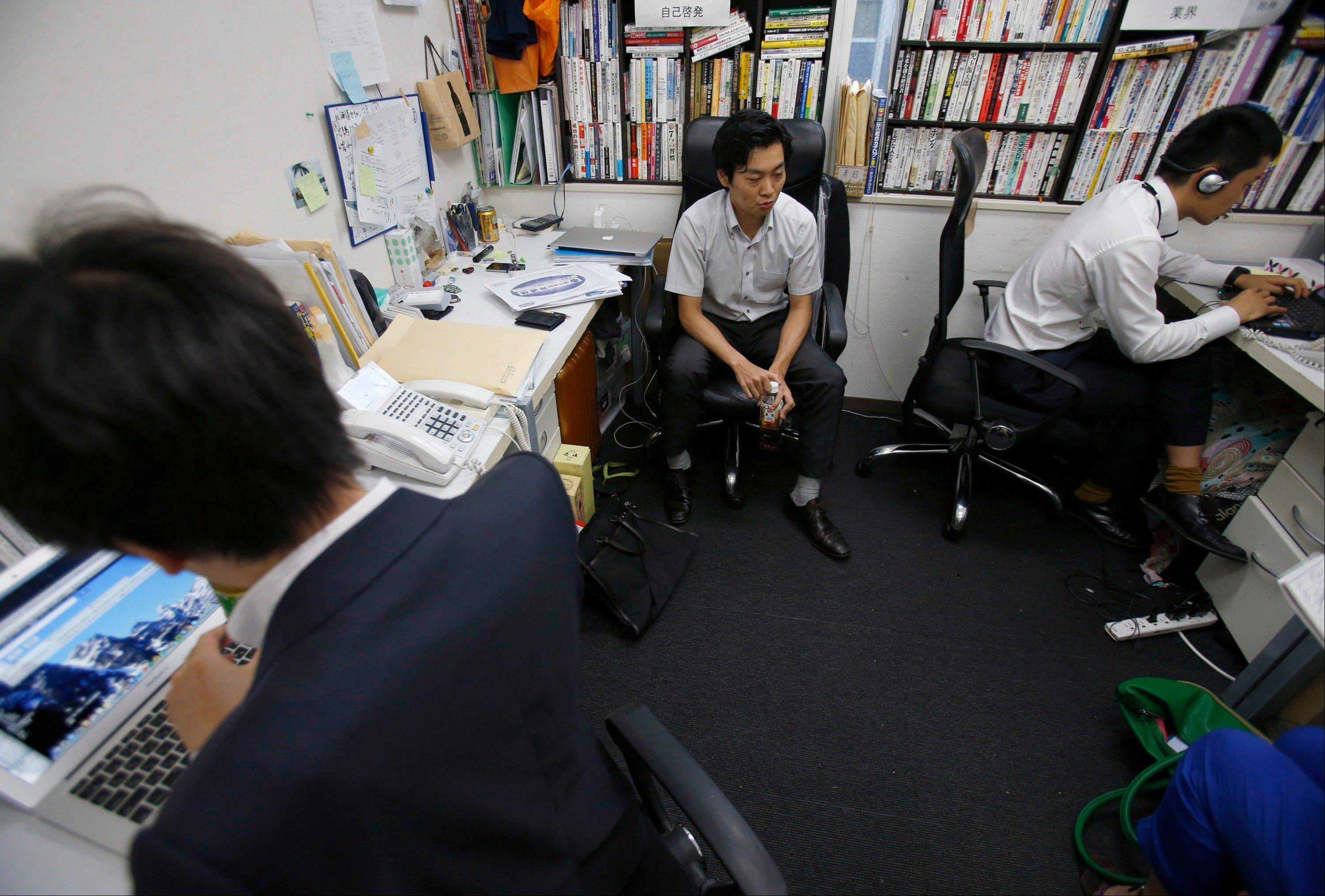 Terra Motors Corp. employee Shimpei Kato, center, speaks during an interview at its headquarters at Tokyo's Shibuya district. Terra is a little know venture that pays far less but is out to conquer the world with its stylish electric scooters.