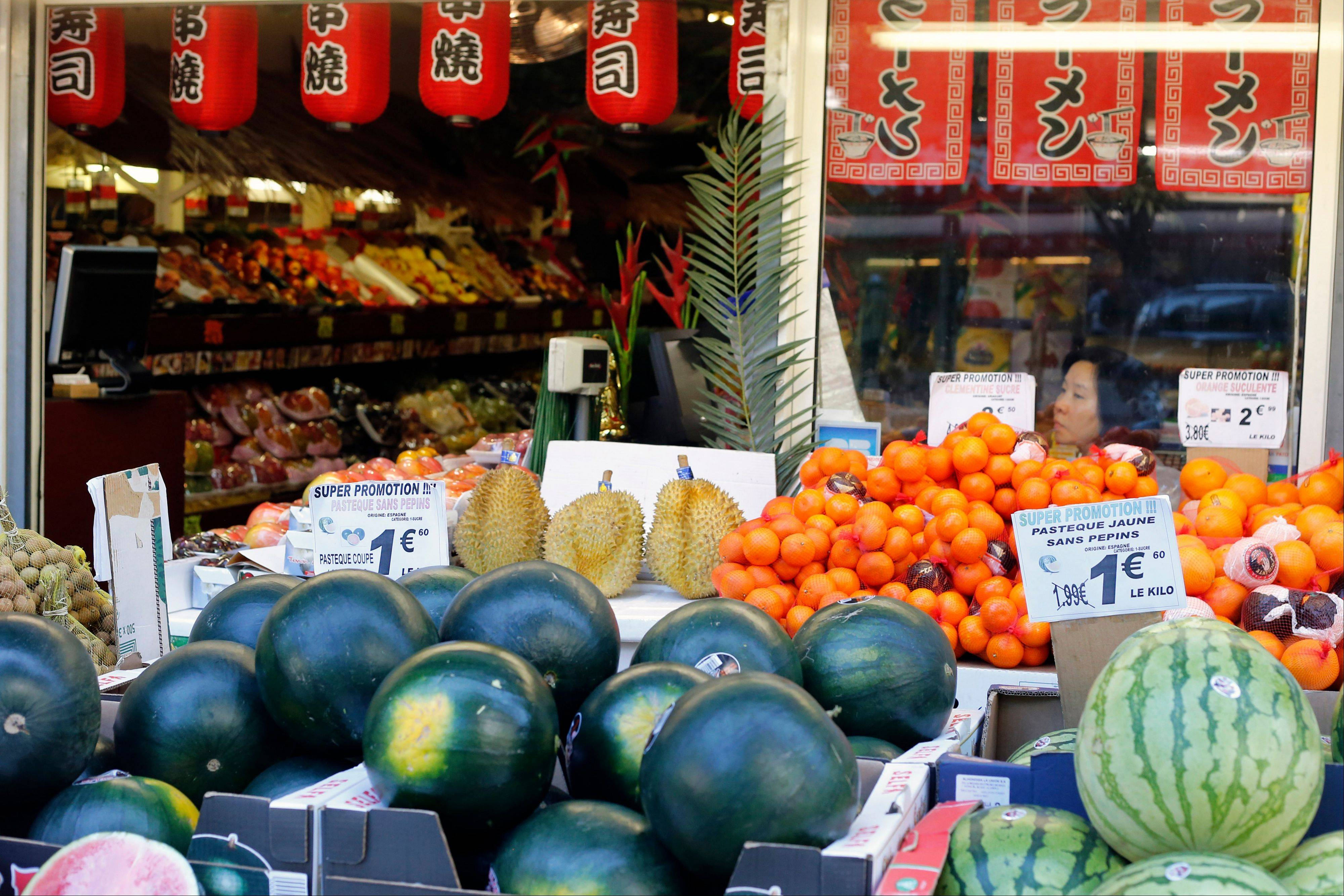 A woman looks out a window at a fruit stand at the Chinese quarter in the 13th district of Paris. This is the largest Chinatown in Europe, and its hidden charms include, among other things, an impressive diversity, drawing on the heritage of French colonies like Vietnam, Cambodia and Laos as well as other parts of Southeast Asia.