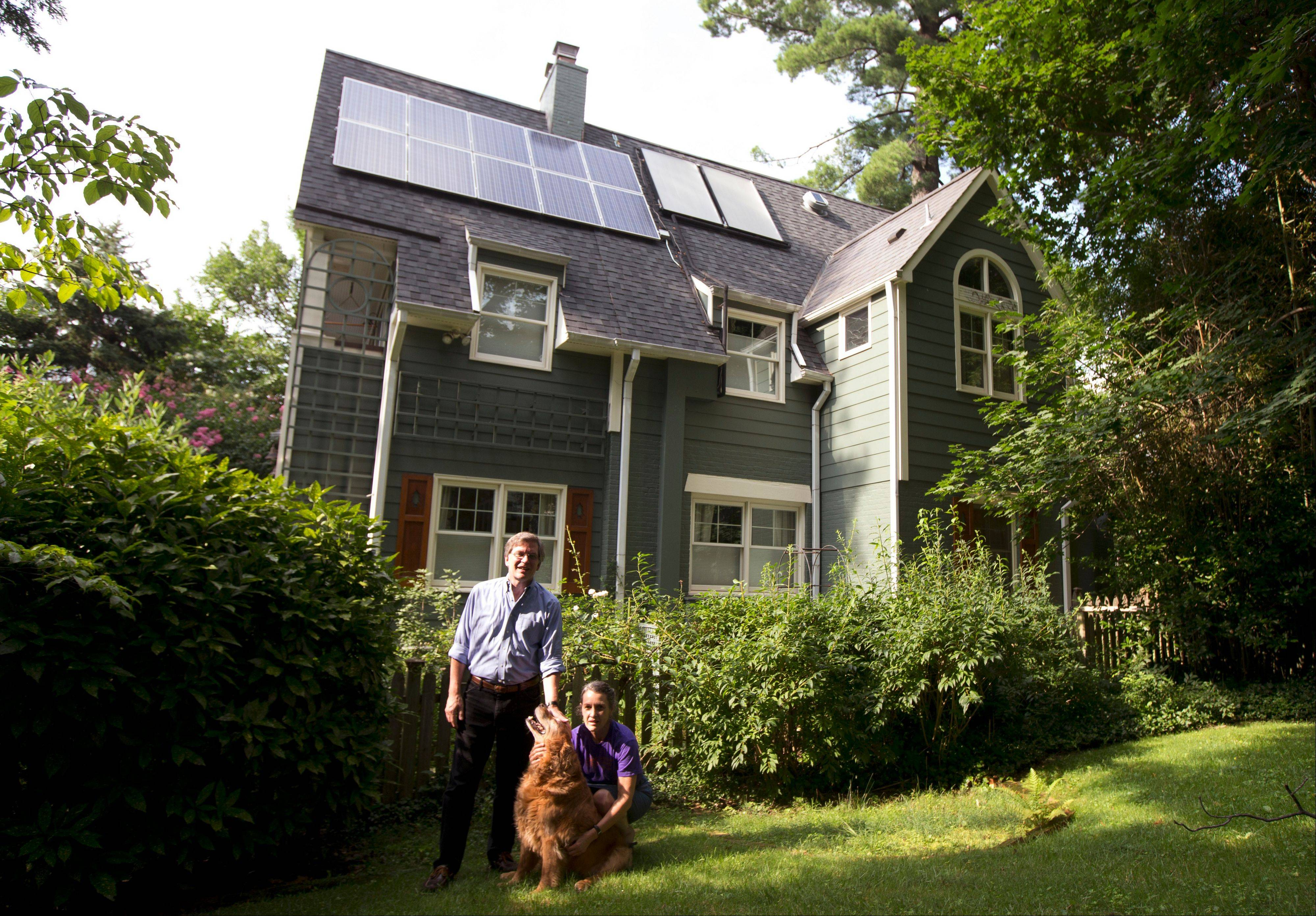 Ketch Ryan, right, and her neighbor, Kirk Renaud, pose next her house with solar panels on the roof in Chevy Chase, Md. They are part of a solar cooperative, Common Cents Solar.