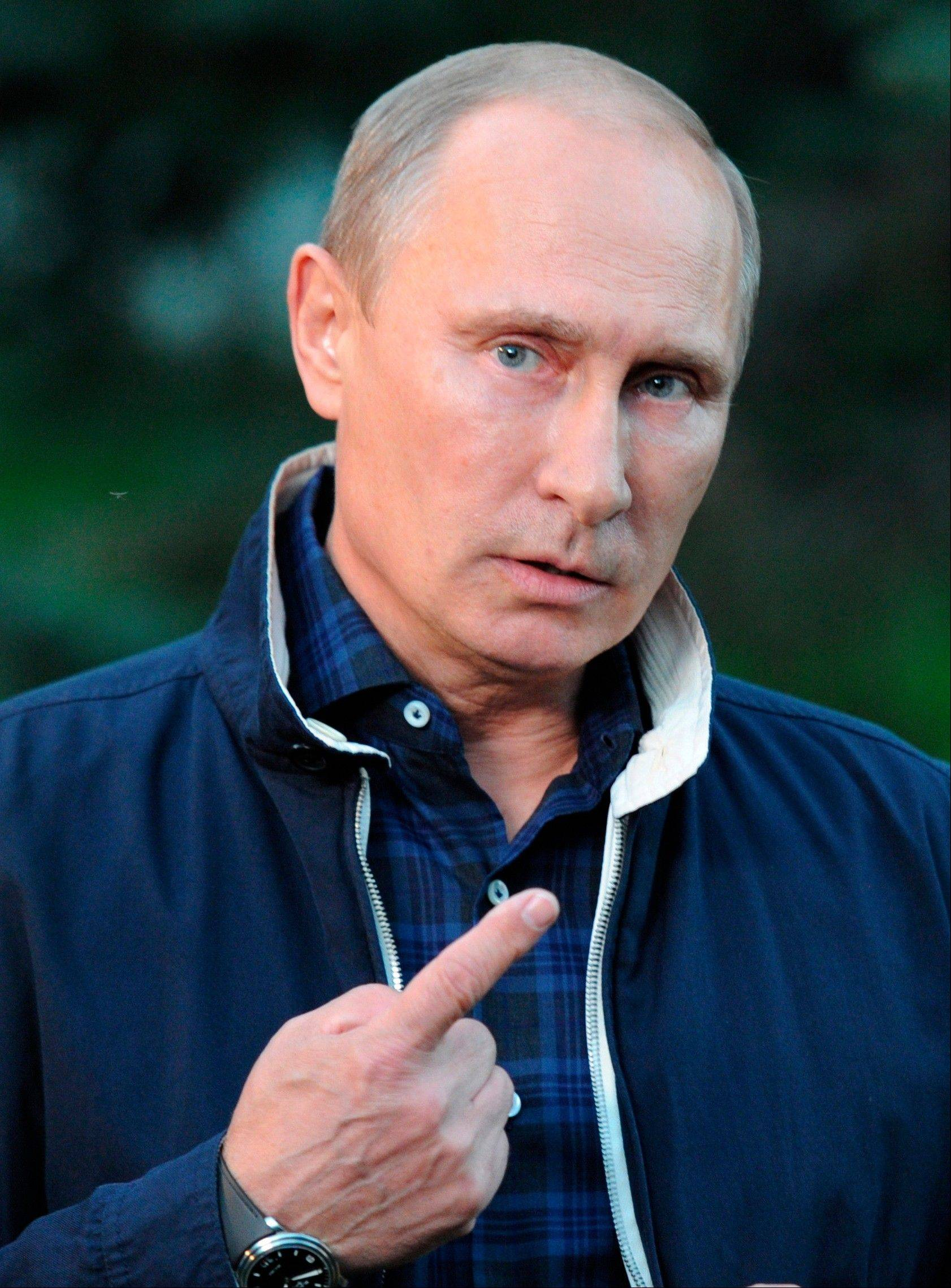 Russian President Vladimir Putin speaks to the media Saturday during his trip to Russia's far eastern port of Vladivostok. Putin urged President Obama not to rush into a decision on striking Syria.