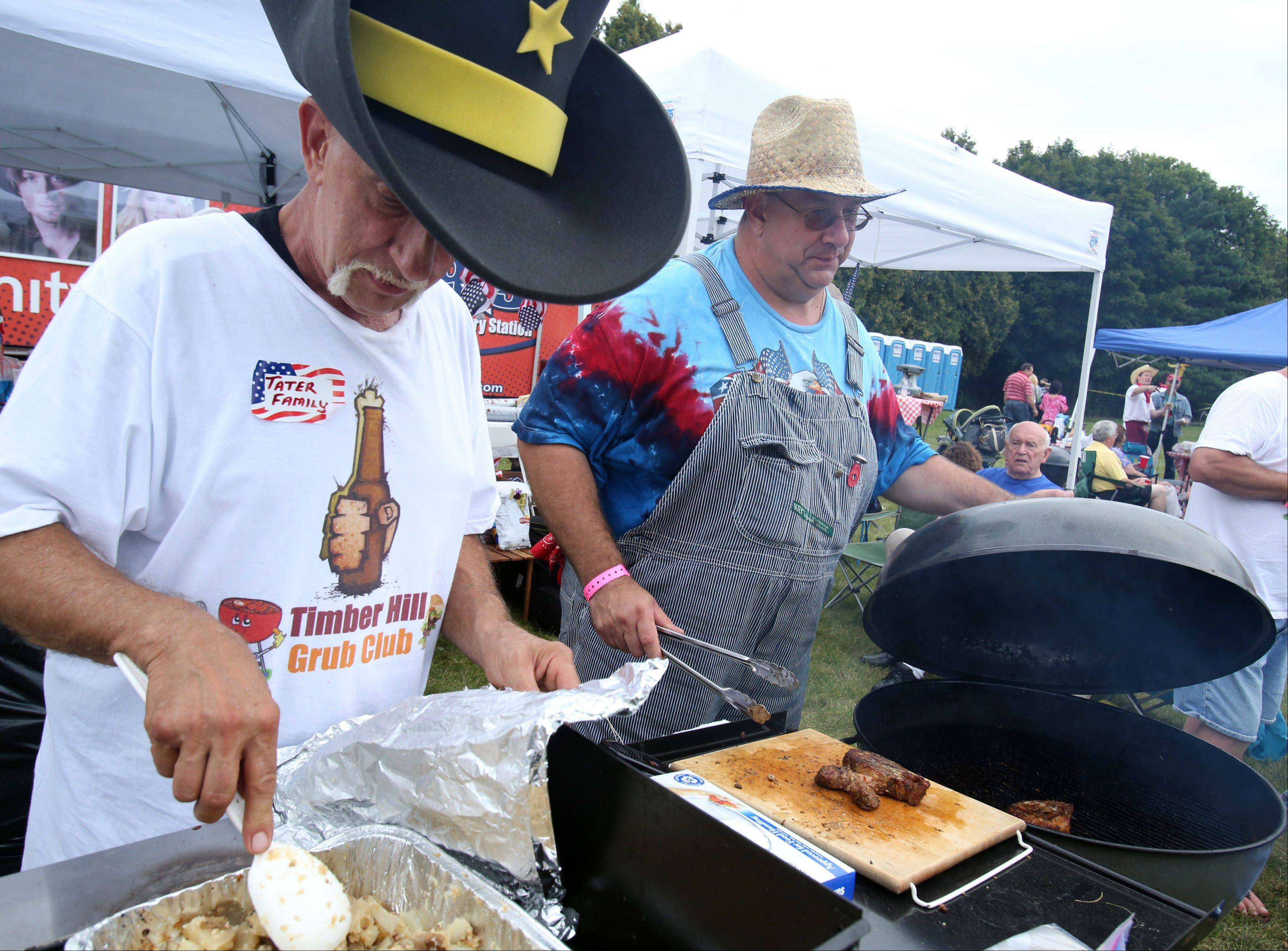 Members of the Timber Hillbillies team including leader John Kirby, of Buffalo Grove, left, and John Klbecka, right, grill in the BBQ cookoff during Buffalo Grove Days Saturday in Buffalo Grove.