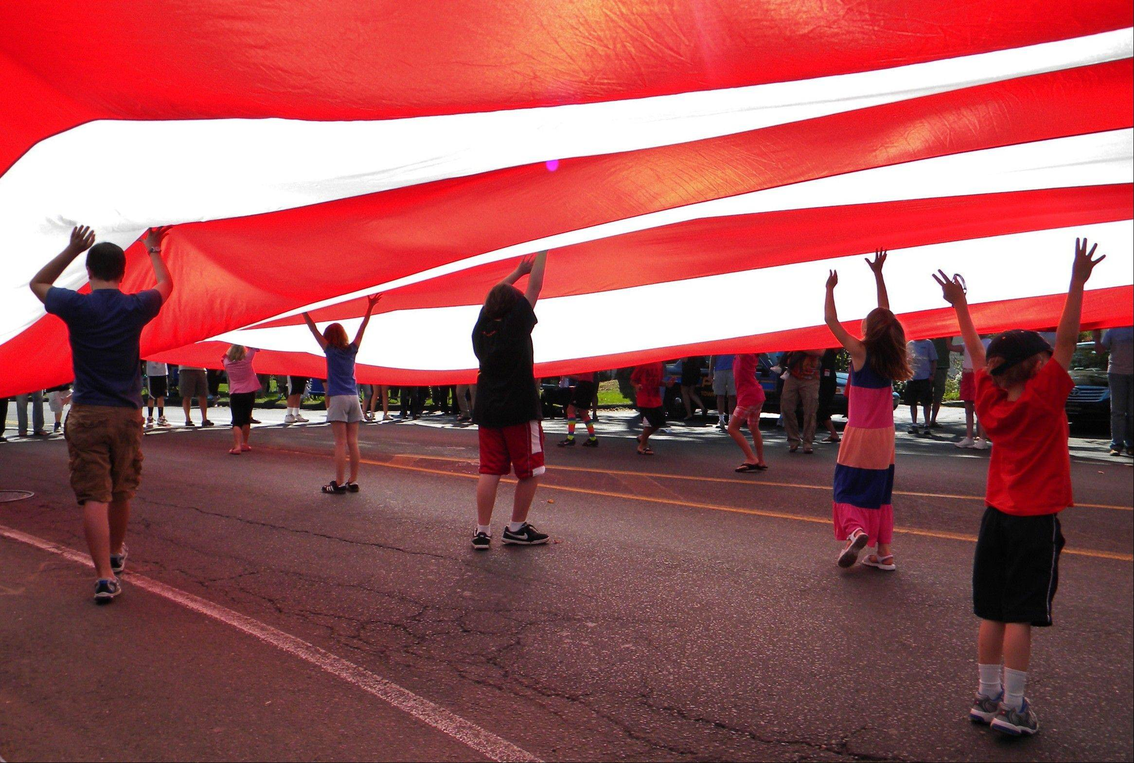 Children hold a flag as it passes down Main Street during the annual Labor Day parade in Newtown, Conn.