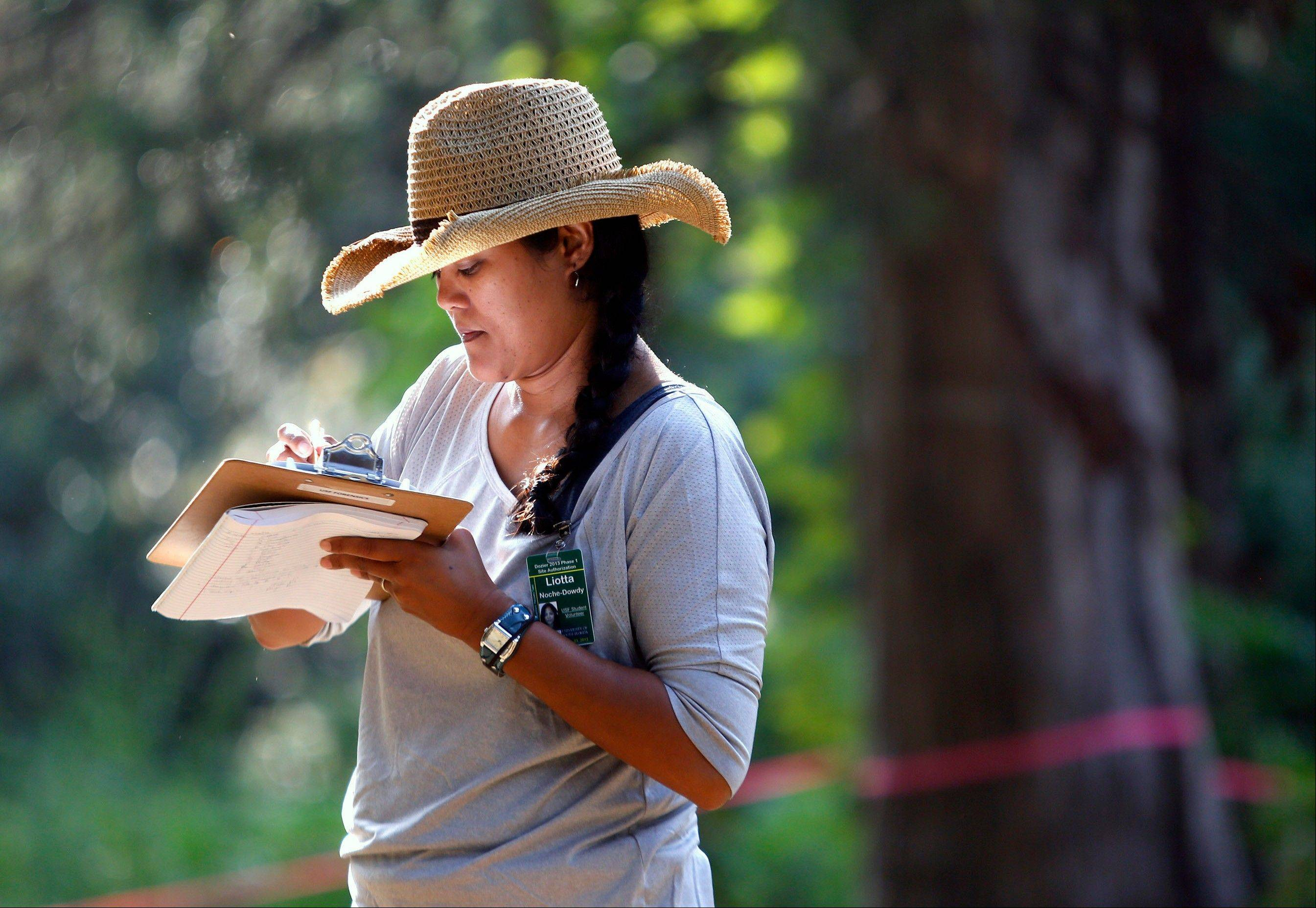 Student volunteer Liotta Noche-Dowdy makes notes as a team of anthropologists from the University of South Florida begin exhuming suspected graves.