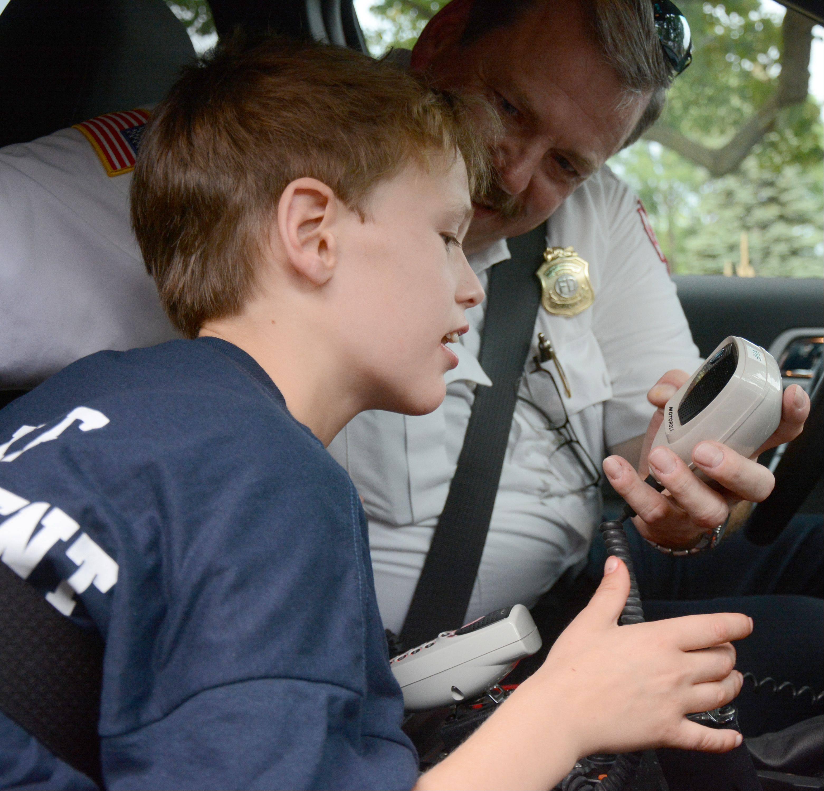 Mount Prospect Deputy Fire Chief Henry Dawson shows Zachary Jakubowski, 11, of Mount Prospect how to work the radio of his SUV during a visit the Mount Prospect Fire Department made to Zachary's home Friday.