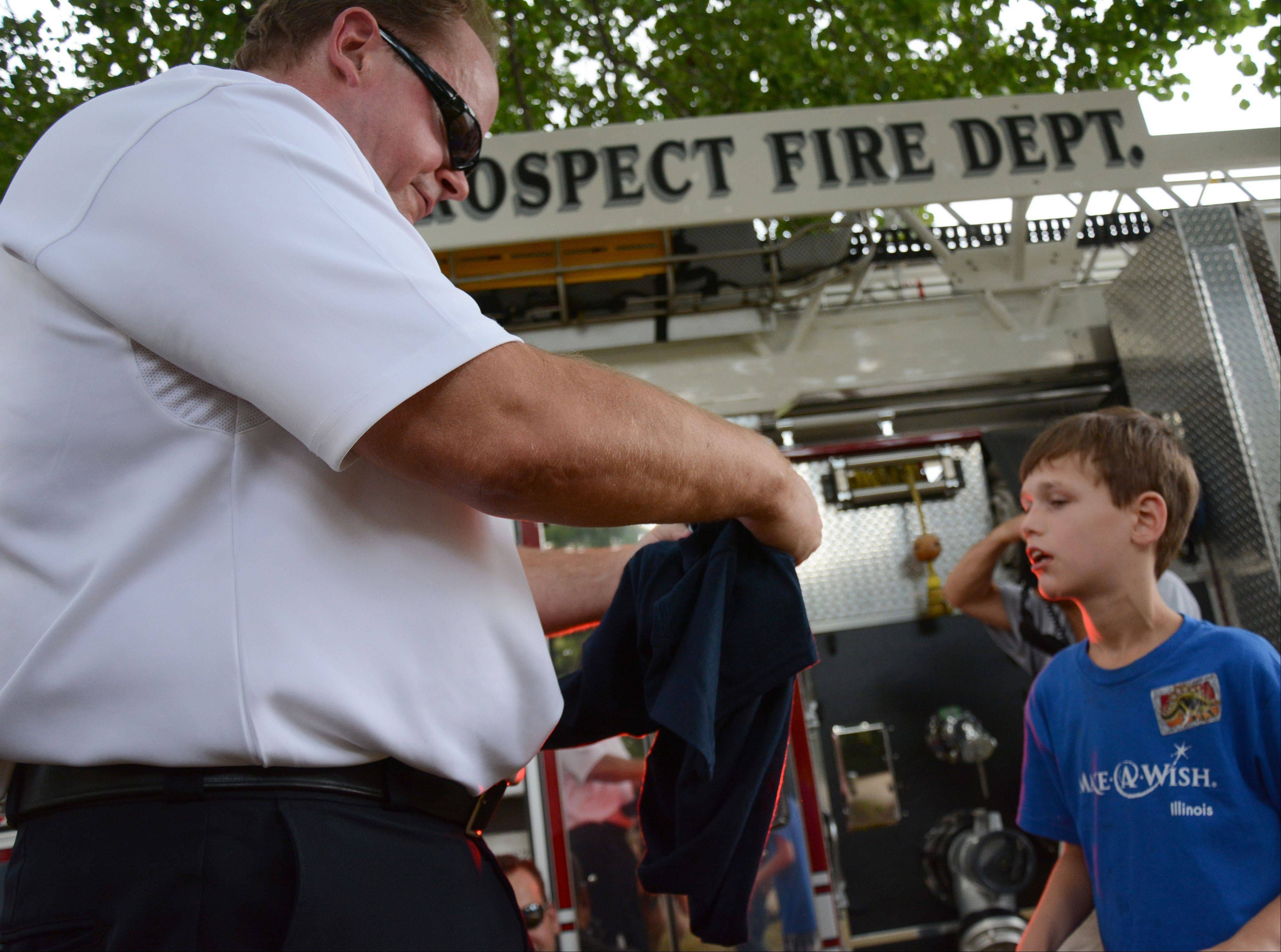 Mount Prospect Fire Chief John Malcolm presents Zachary Jakubowski, 11, of Mount Prospect an official fire department T-shirt during a visit Friday.