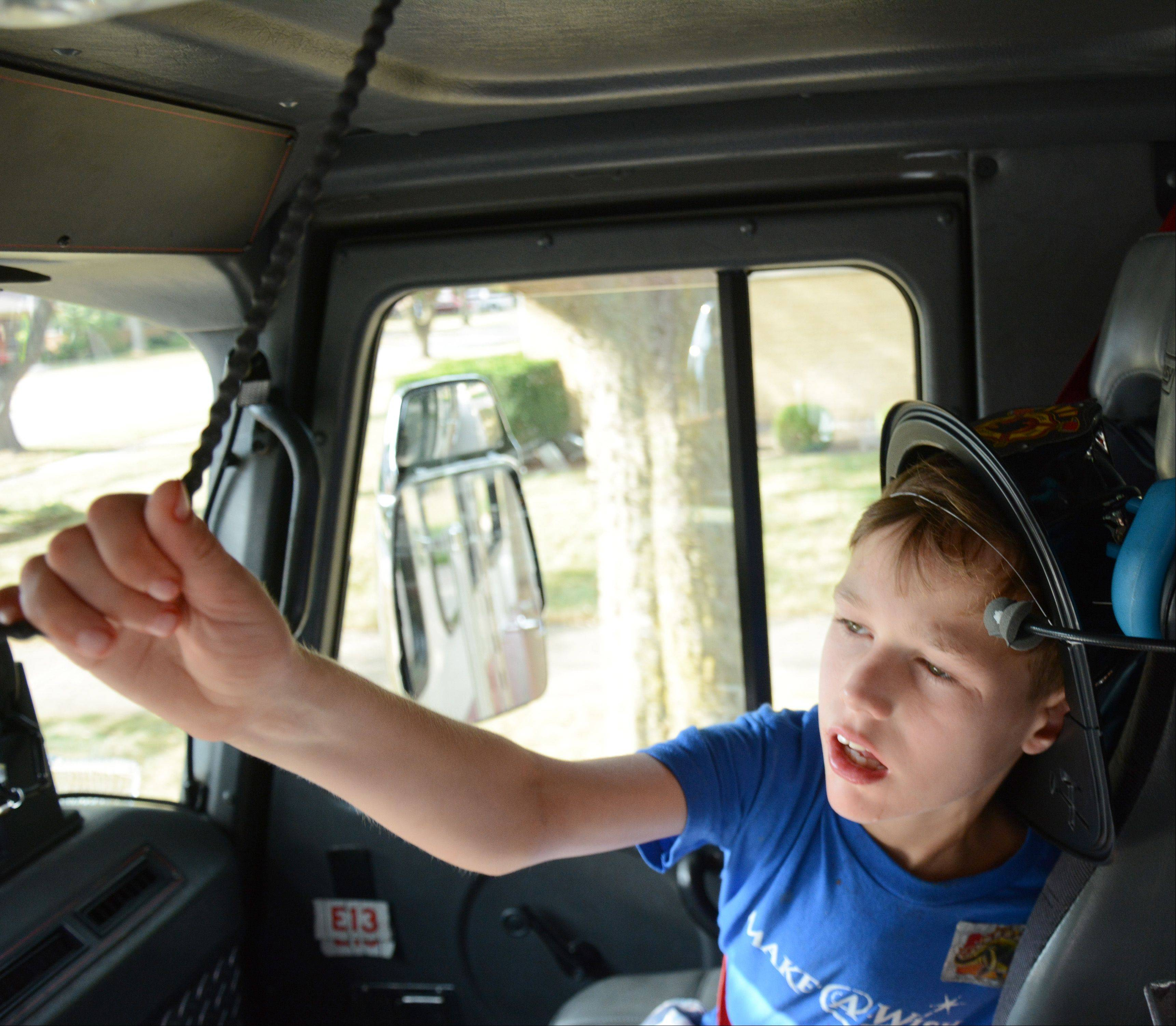 Zachary Jakubowski, 11, of Mount Prospect pulls the air horn during his ride along in a fire engine Friday.