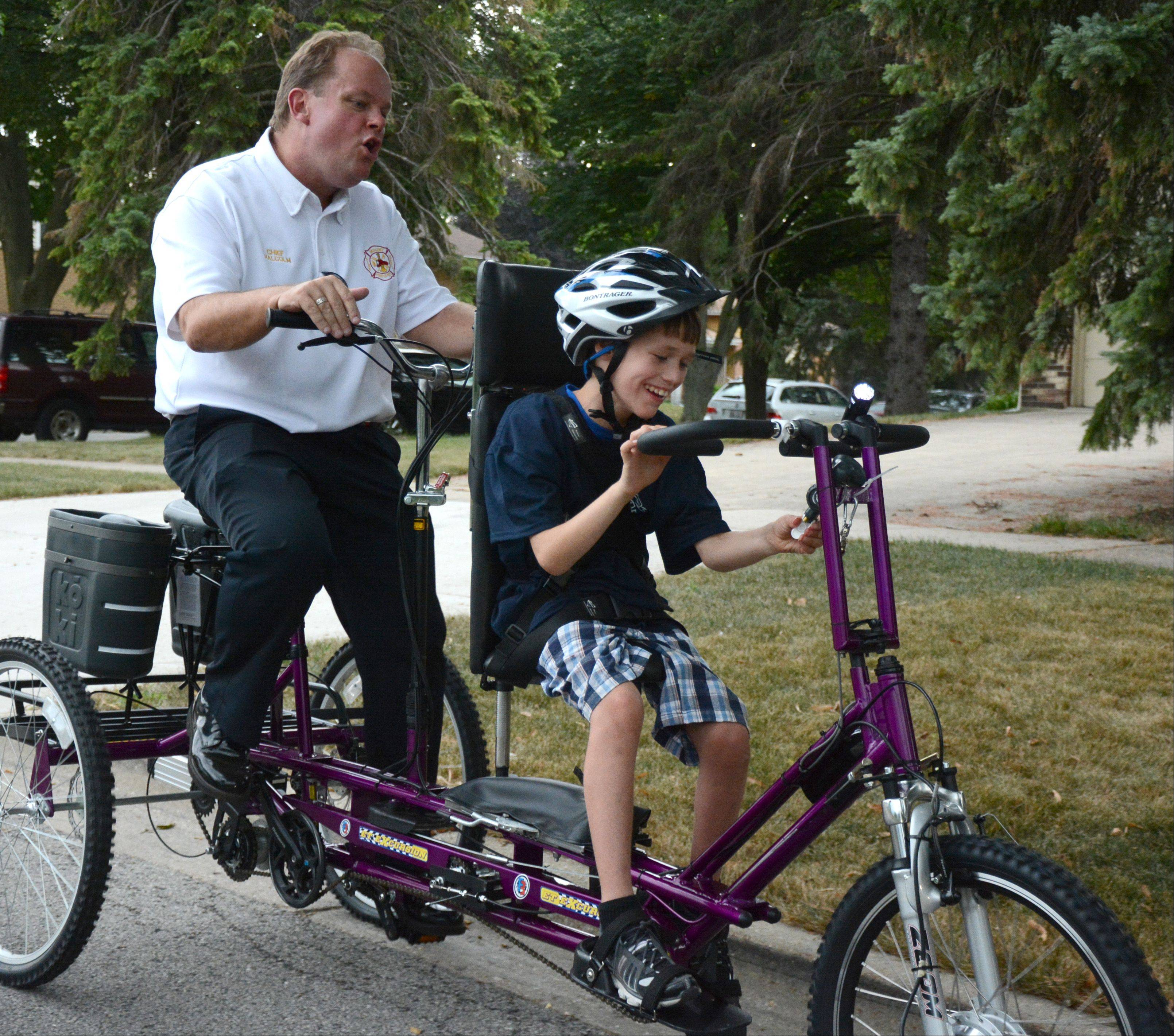 Mount Prospect Fire Chief John Malcolm and Zachary Jakubowski, 11, of Mount Prospect take a ride on Zachary's new adaptive bicycle that came with a fire truck horn Friday.