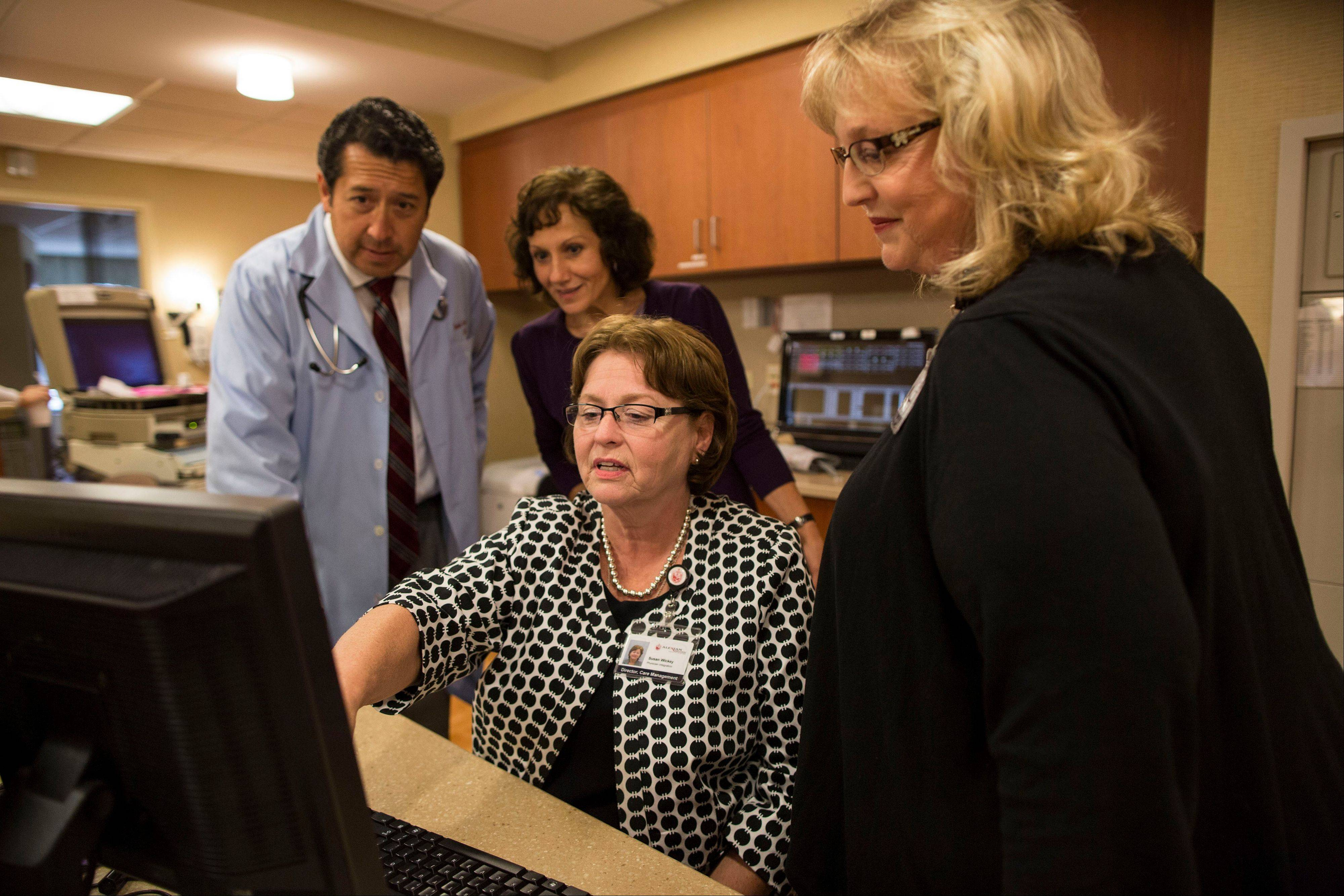 Dr. Reinhold Illerna, from left, Administrative Director of Case Management at Alexian Brothers Healthcare Center, Mary Schumann, Director of Care Management at Alexian Brothers Healthcare Center, Sue Wickey and Manager of Social Work at Alexian Brothers Healthcare Center, Jolene Grabowski work on a computer at the nurses station at the Alexian Brothers Healthcare Center in Elk Grove Village.