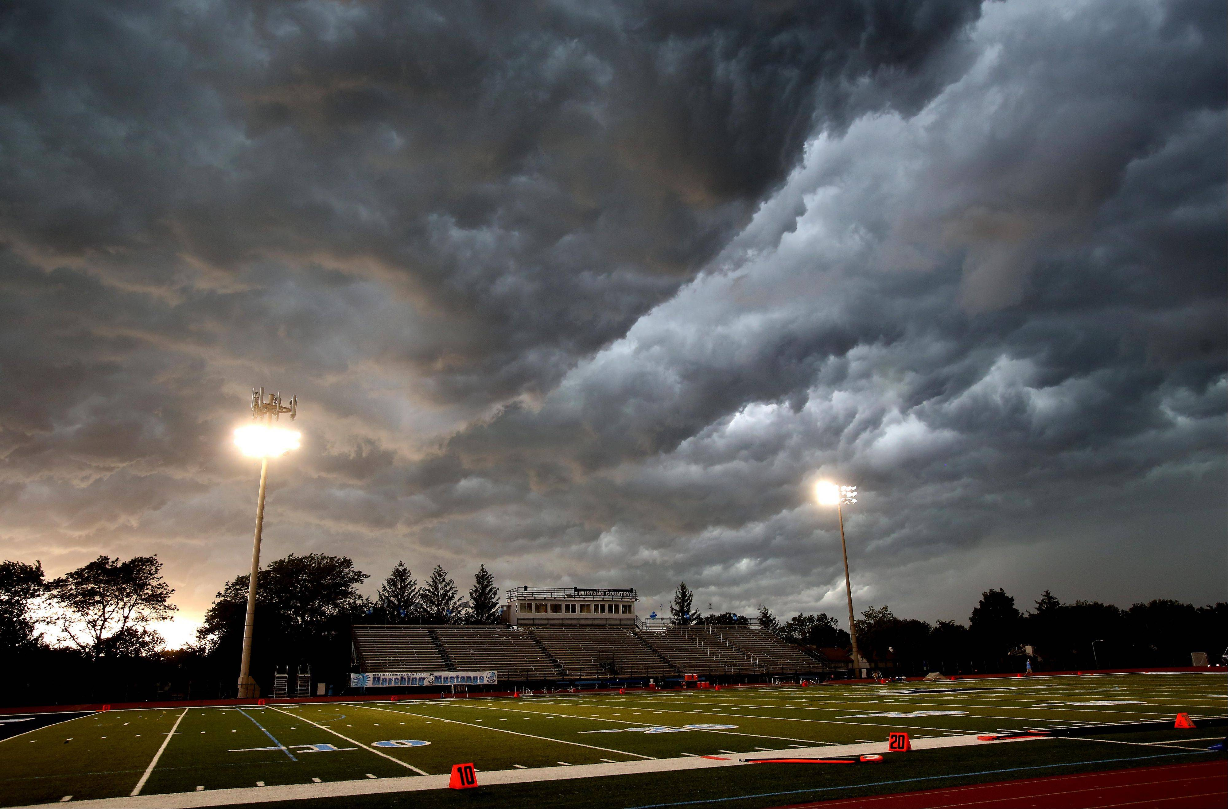 Storm clouds move over an empty football field after the stadium was cleared for the Benet vs. Downers Grove South sophmore football game on Friday in Downers Grove.
