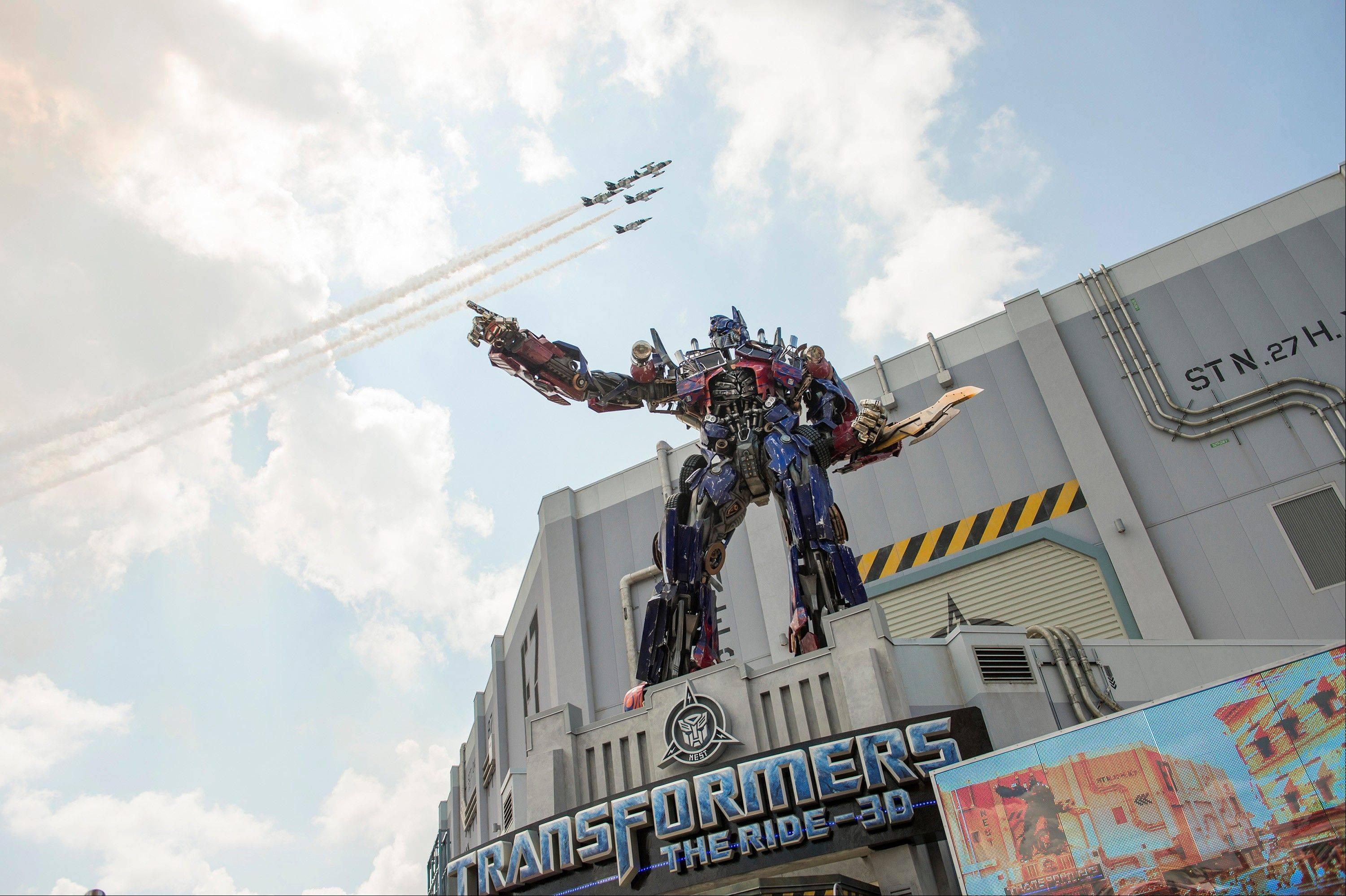 A three-story-tall Optimus Prime figure stands at the entrance to the Transformers: The Ride-3D as a formation of private jets flies overhead at the grand opening of the attraction at Universal Orlando Resort in Orlando, Fla.