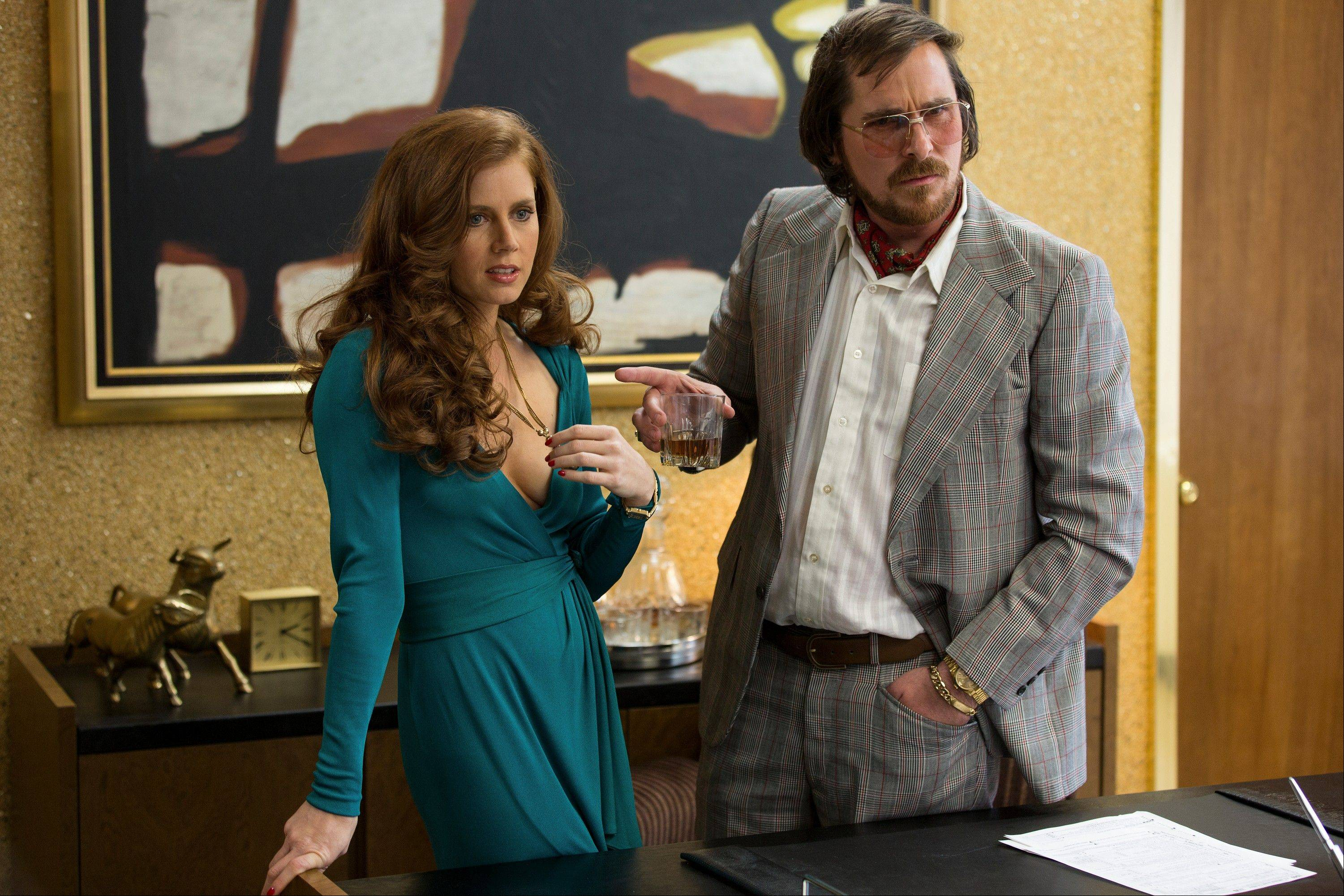 "Amy Adams, left, and Christian Bale in a scene from ""American Hustle."""