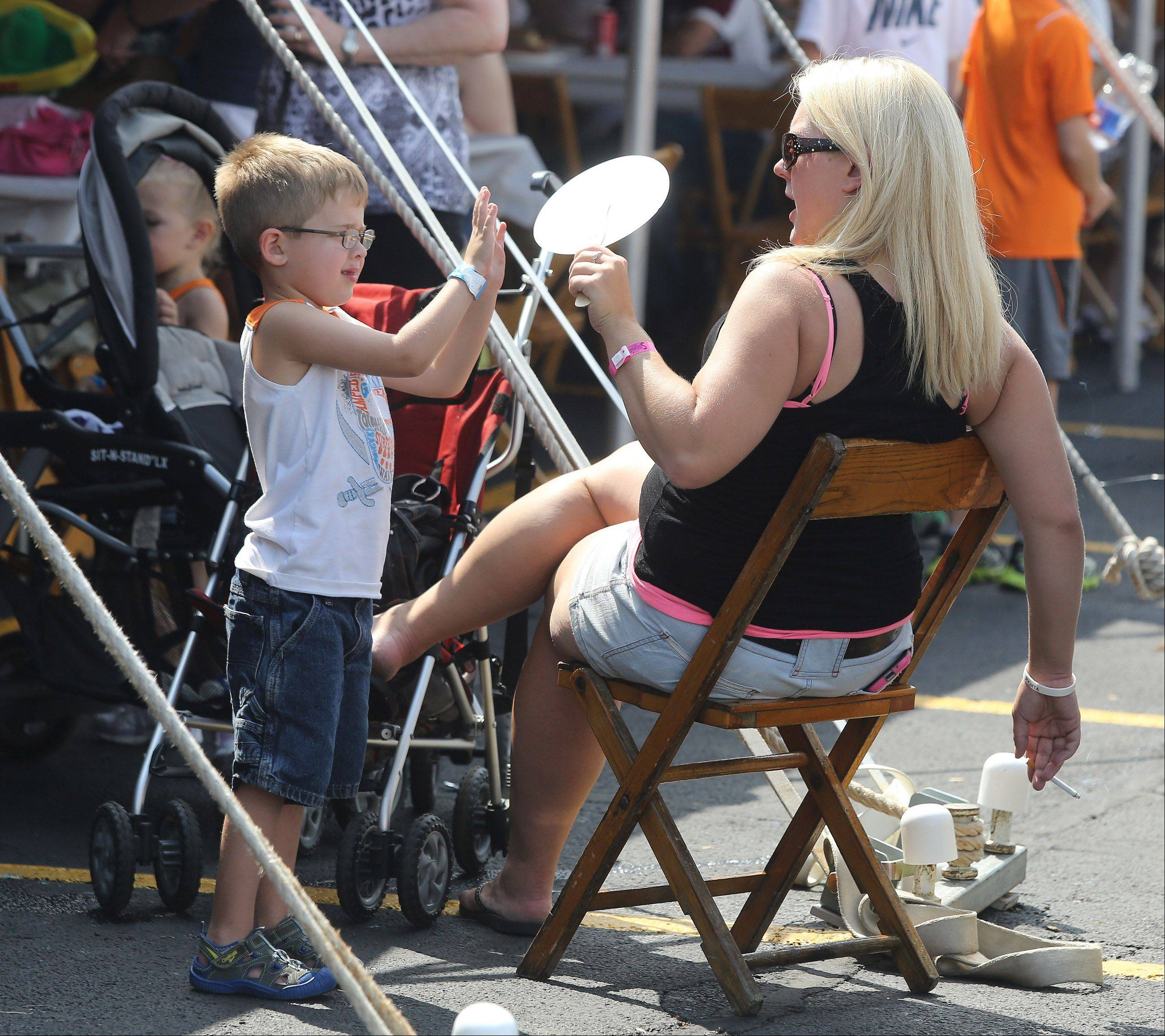 Schaumburg resident Ashley Anderson fans her son Connor, 4, as they eat at the food tent during the second day of Schaumburg Septemberfest Sunday. The festival featured food, carnival, games and entertainment.