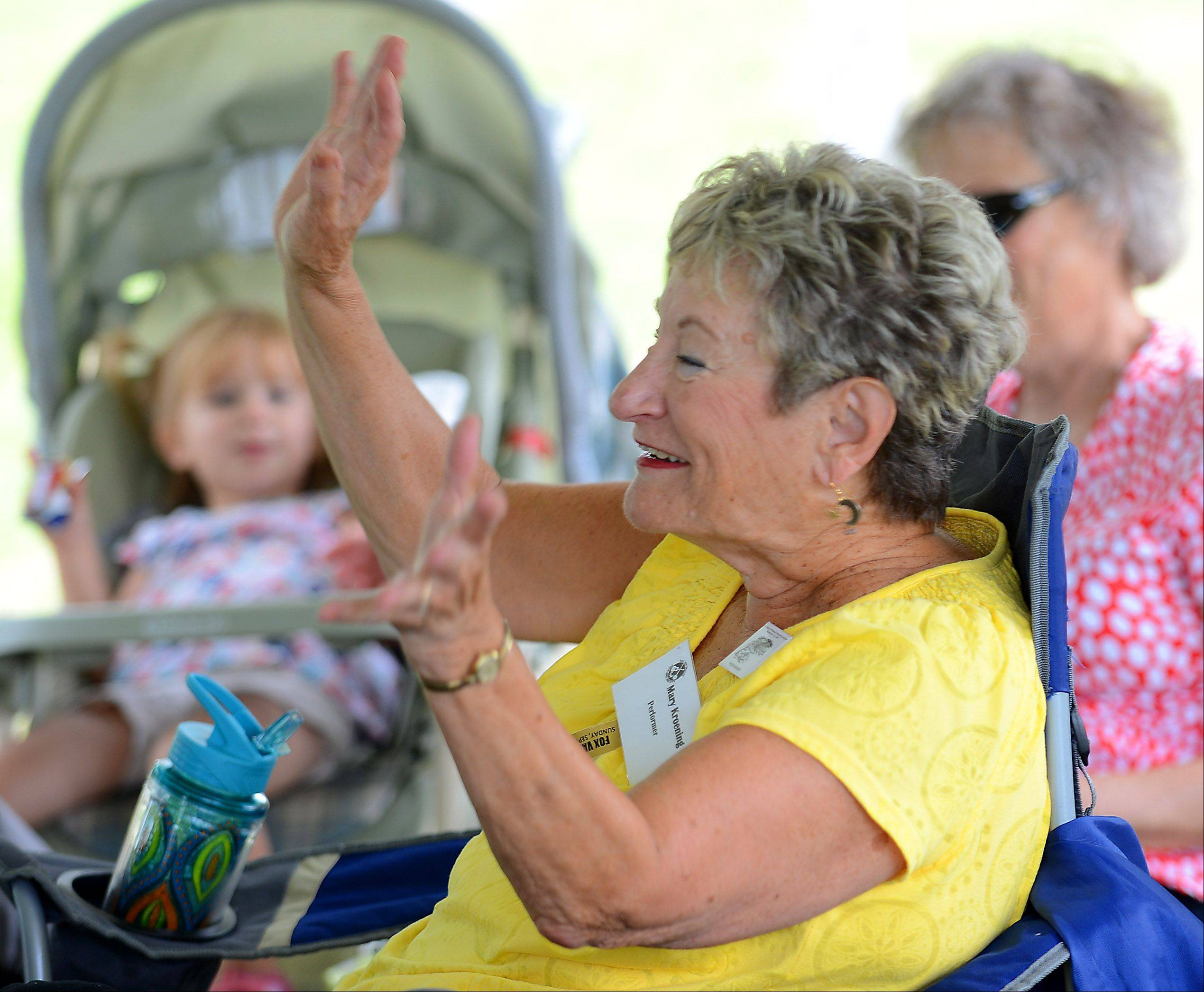 Mary Kroening of Naperville plays along with a storyteller on stage in raising a commotion during the 37th annual Fox Valley Folk Music and Storytelling Festival at Island Park in Geneva Sunday. She's also a storyteller and was going to perform later.