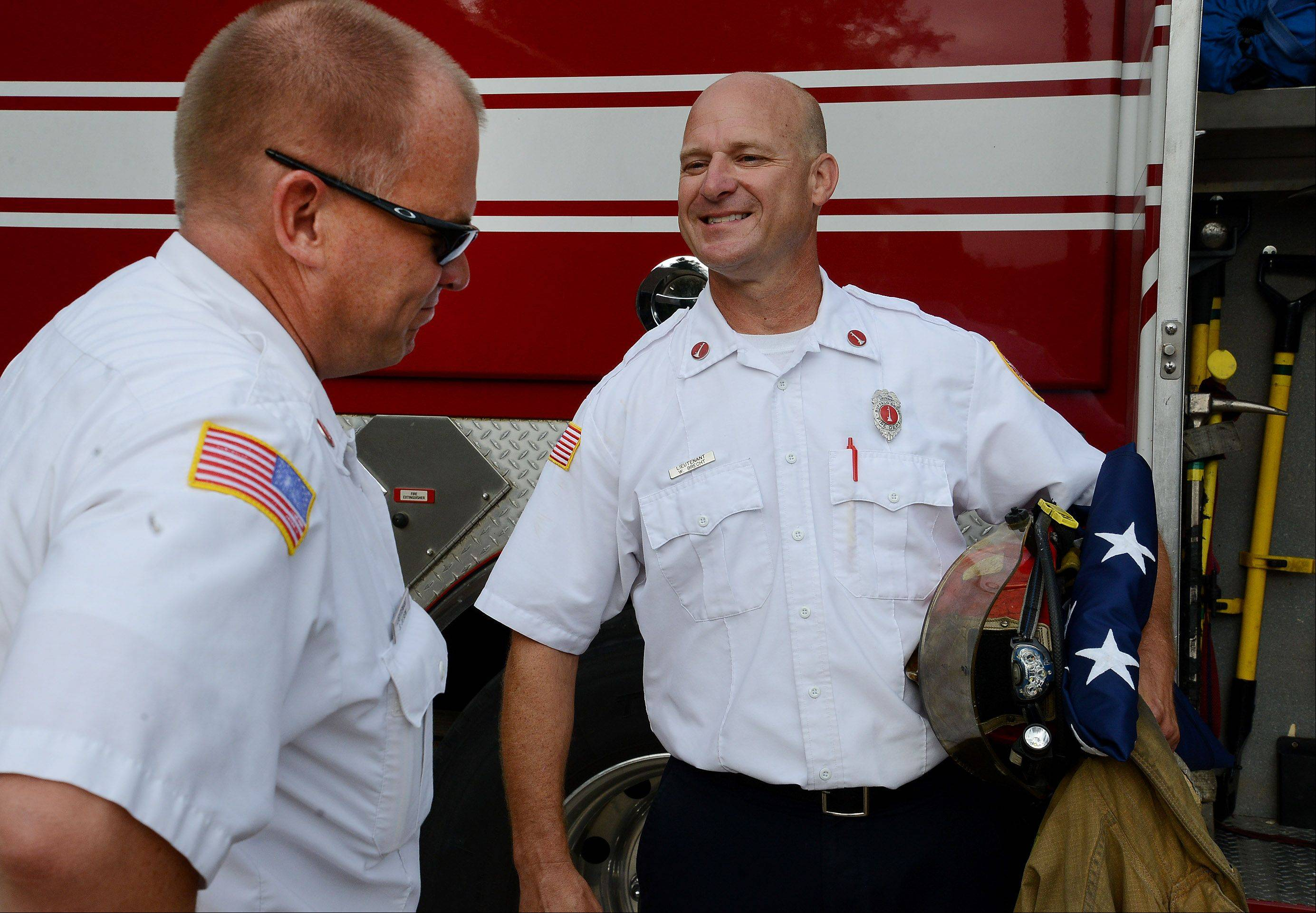"Buffalo Grove Fire Department Lieutenant William ""Kent"" Brecht, right, is congratulated by his good friend Lieutenant Scott Olson on the occasion of his retirement after 25 years with the department."