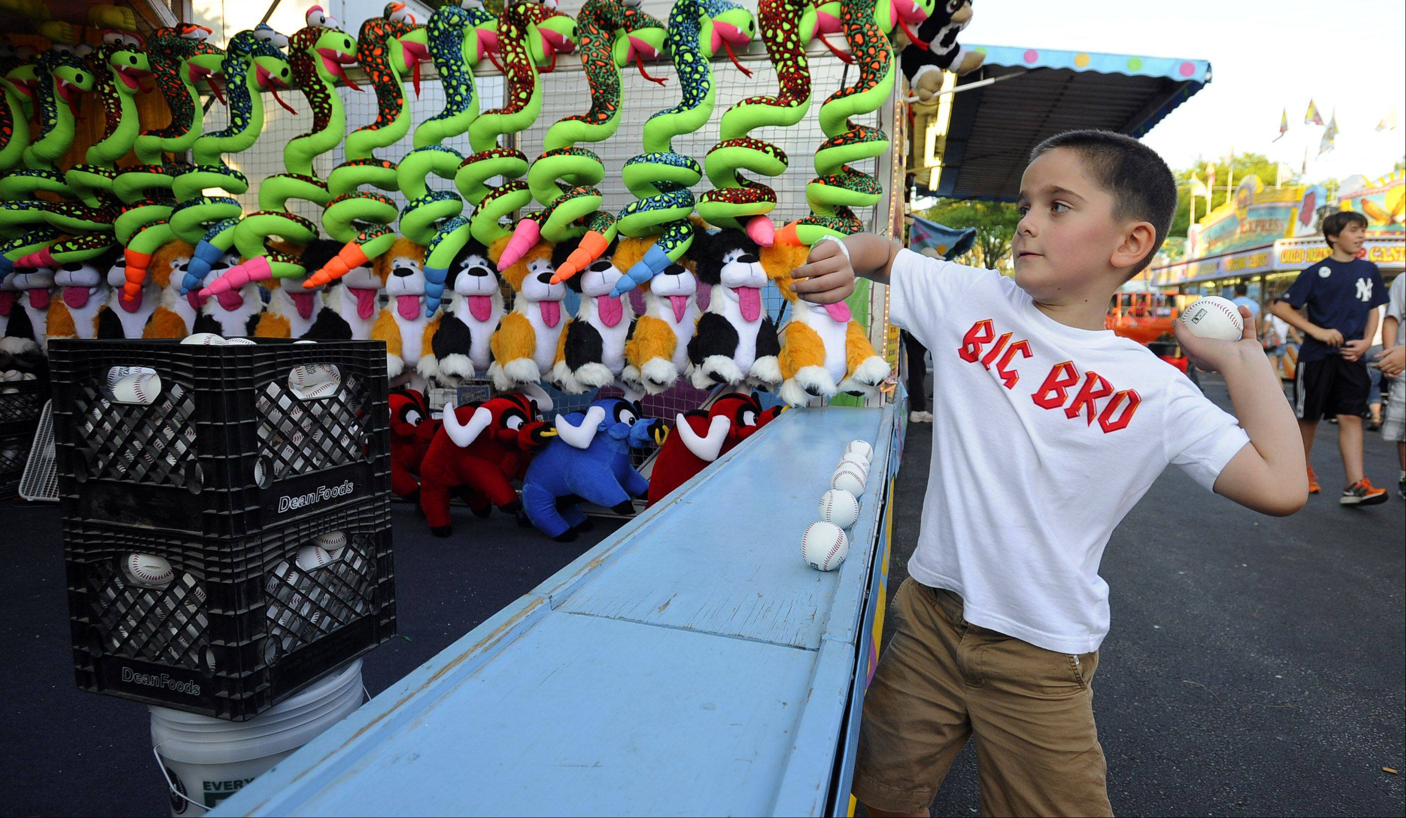 Carson Stech, 6, delivers his fastball at the baseball game at opening night at Buffalo Grove Days on Thursday.