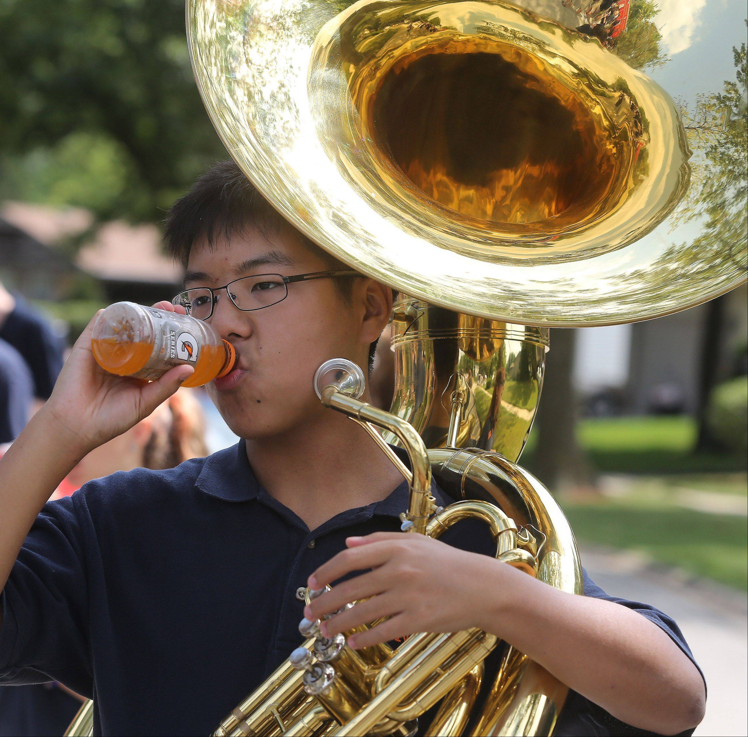 Buffalo Grove High School marching band member Christian Yi tries to keep cool Sunday as he drinks Gatorade while holding his sousaphone during the Buffalo Grove Days parade.