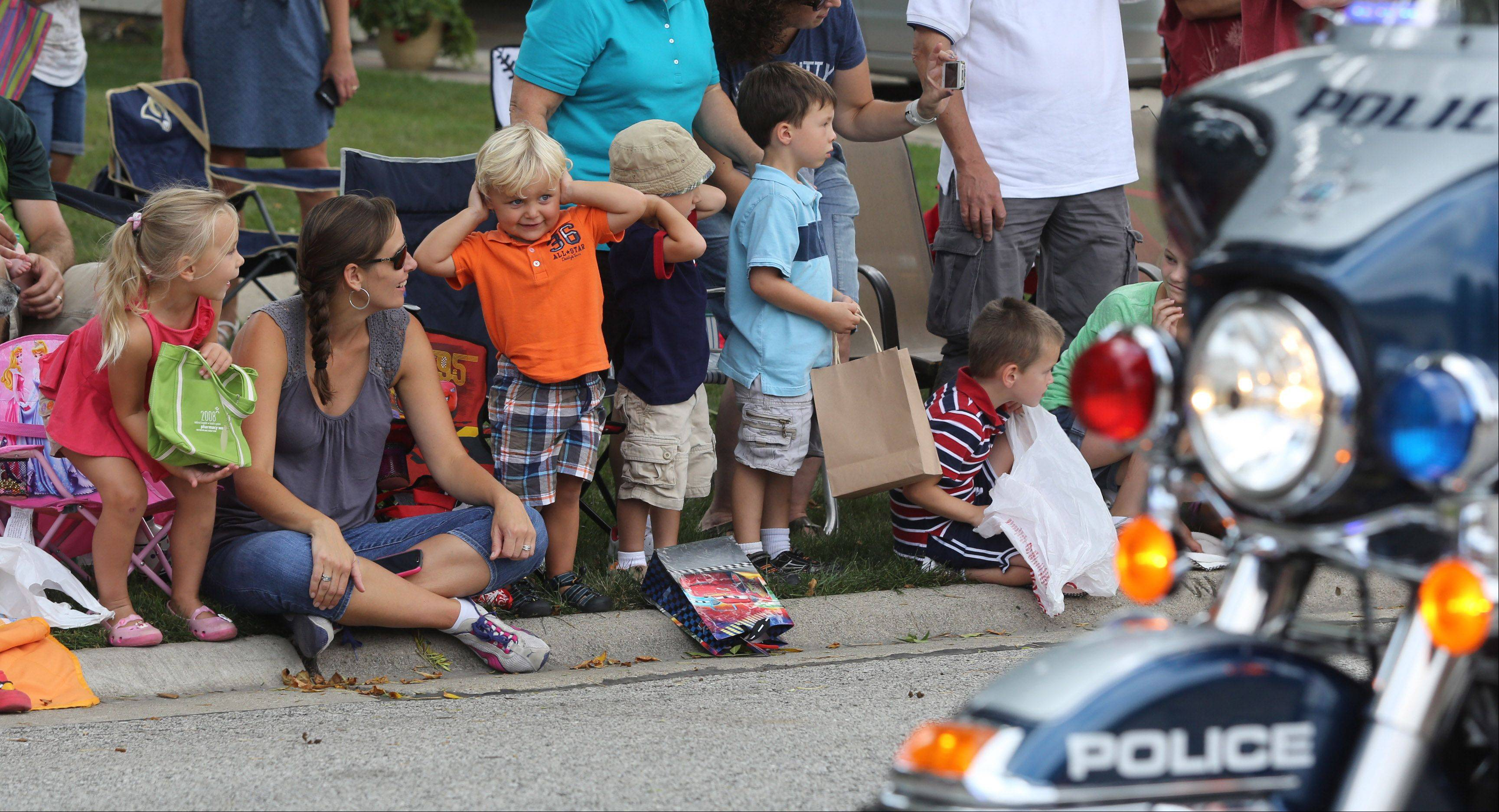 Two-year-olds Dean Jacob, in orange, and Hunter Wojcik cover their ears Sunday as the police sirens sound during the Buffalo Grove Days parade.