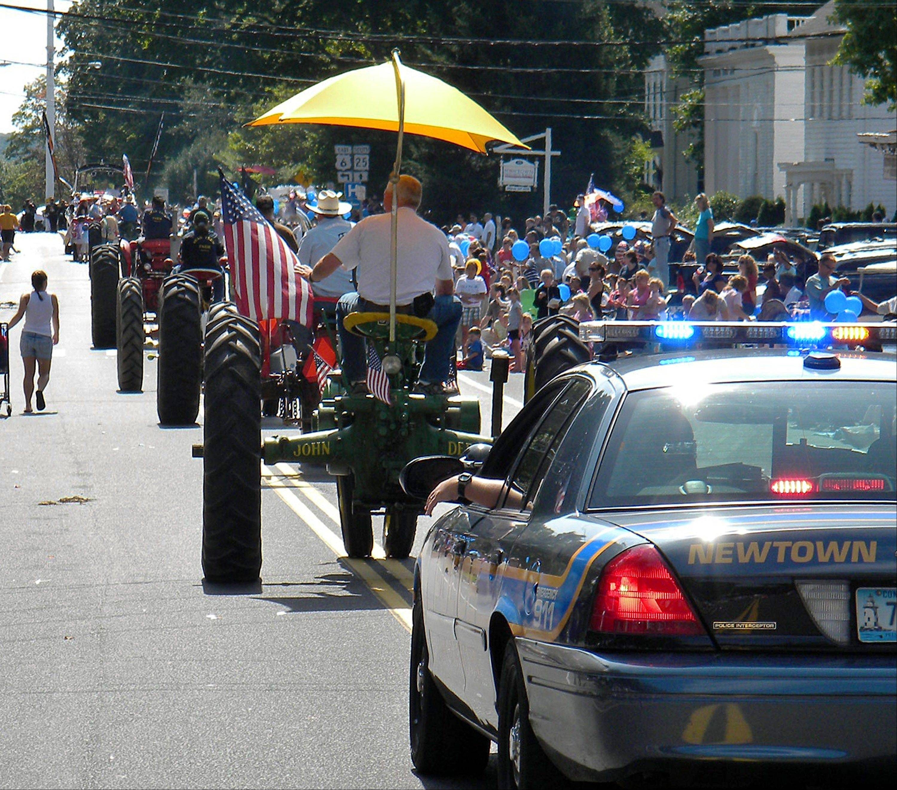A convoy of modern and antique tractors with a police escort brings up the rear of the Labor Day parade in Newtown, Conn. The town's annual parade for 2013 comes nearly nine months after shootings at Sandy Hook Elementary School left 26 dead, 20 of them children.