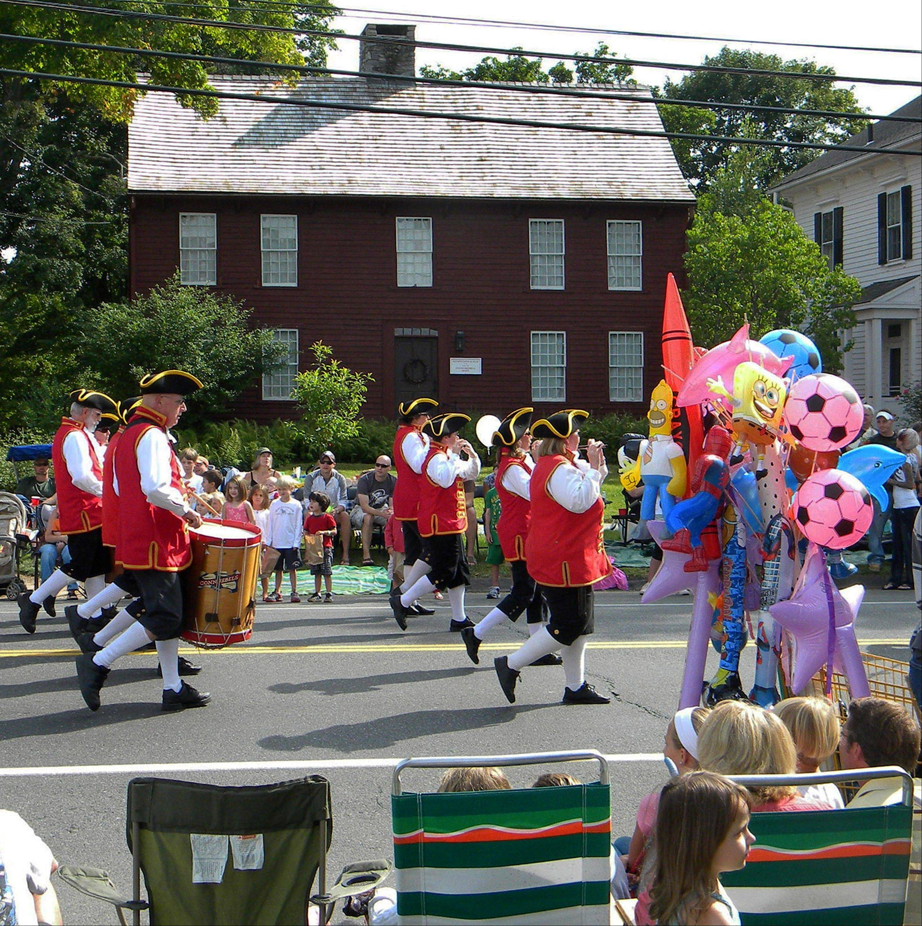 A fife-and-drum band in colonial-era uniforms marches past a souvenir seller and spectators during the Labor Day parade in Newtown, Conn. The parade has been a town fixture since Sept. 3, 1962.