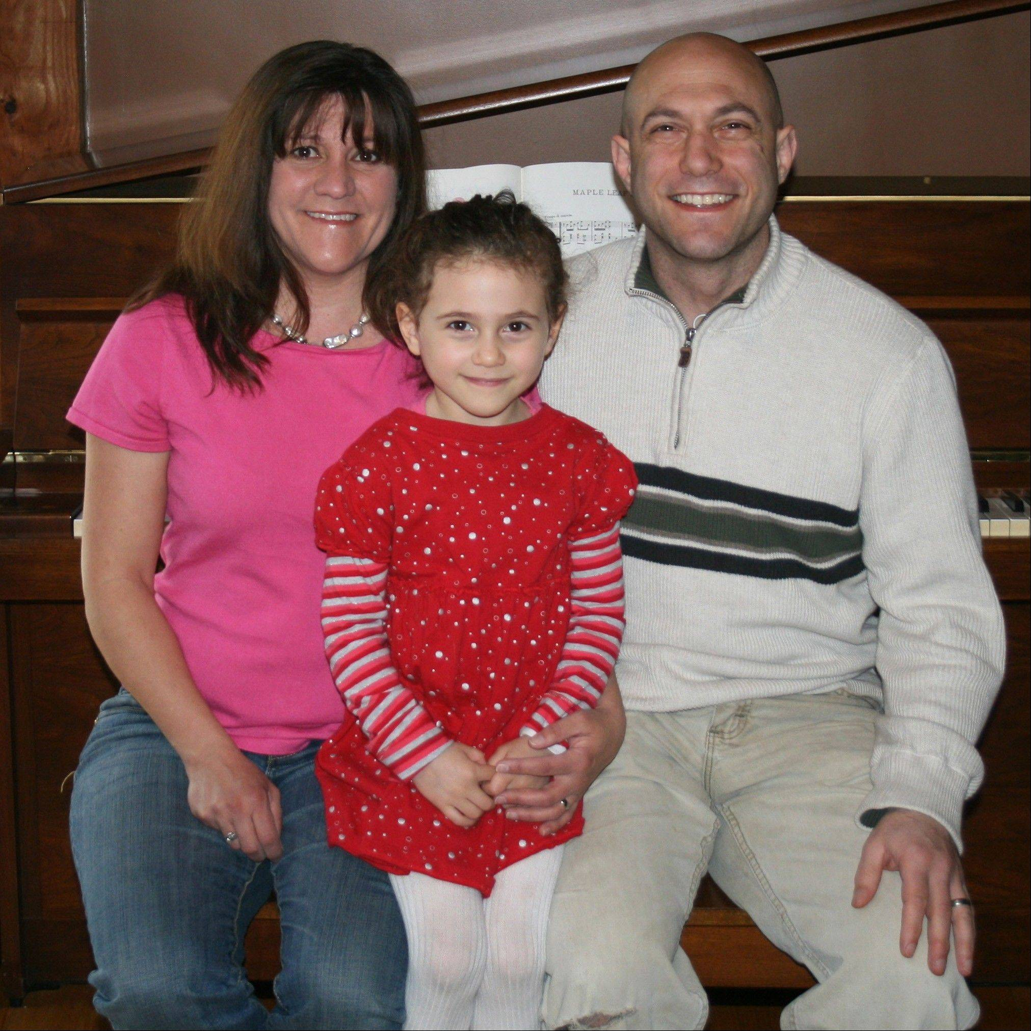 "This April 2012 photo provided by the family shows Avielle Richman, center, with her parents Jennifer Hensel and Jeremy Richman in Boston. Avielle was among the 20 children killed in the Dec. 14, 2012 Sandy Hook Elementary School shooting. In On Labor Day 2013, Hensel and Richman will walk in Newtown's parade behind a banner for the foundation named after their daughter, which supports research into the brain pathologies behind violence. It also promotes community outreach, so that isolated, vulnerable individuals, like the accused shooter, are not ignored. ""I feel that a way for us to heal is to pull into the community,"" Hensel said. So they'll march, thinking of their daughter, her husband said. ""Avielle loved parades."""