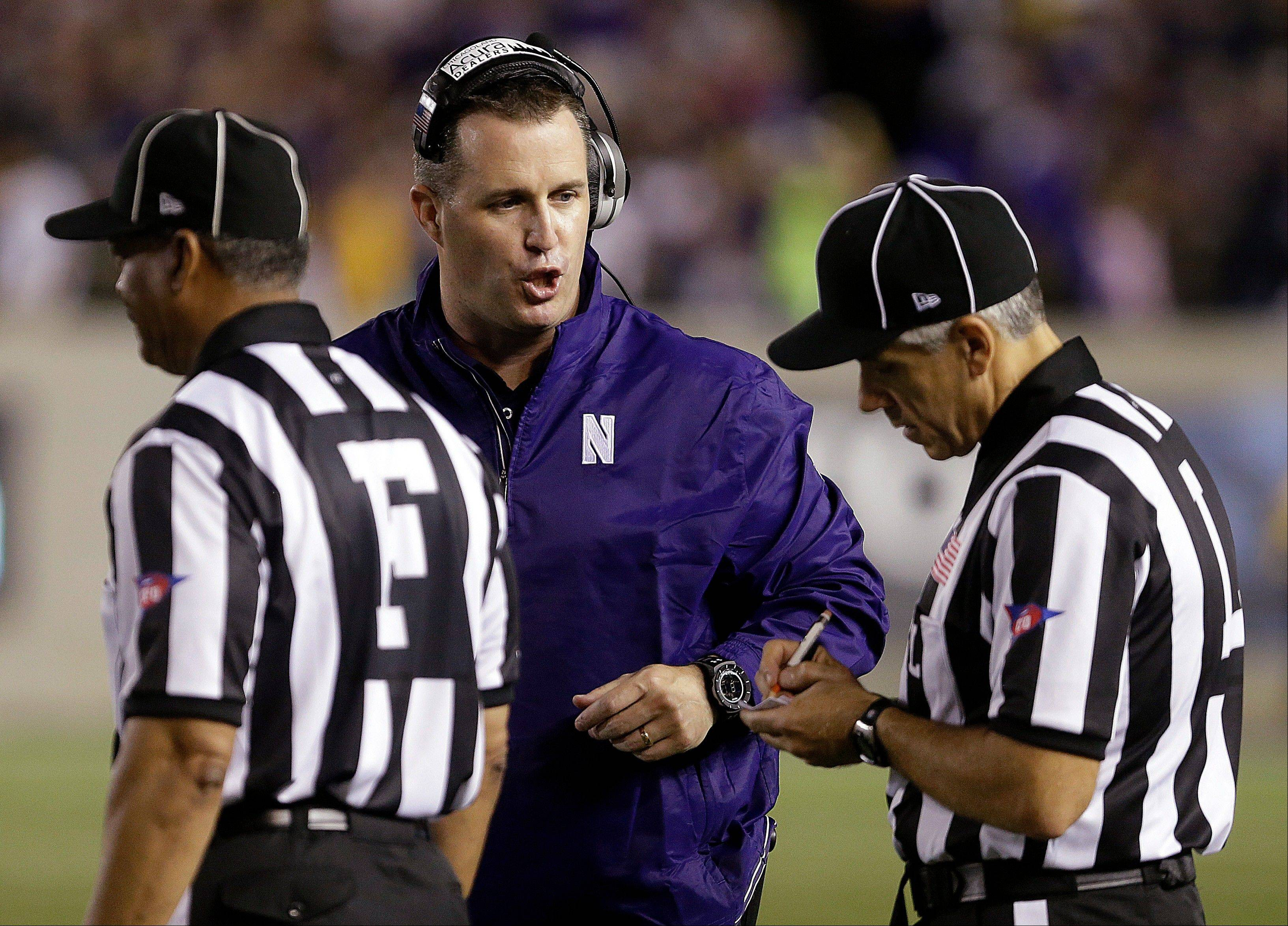 Northwestern coach Pat Fitzgerald speaks with referees during the first half of an NCAA college football game against California on Saturday, Aug. 31, 2013, in Berkeley, Calif.