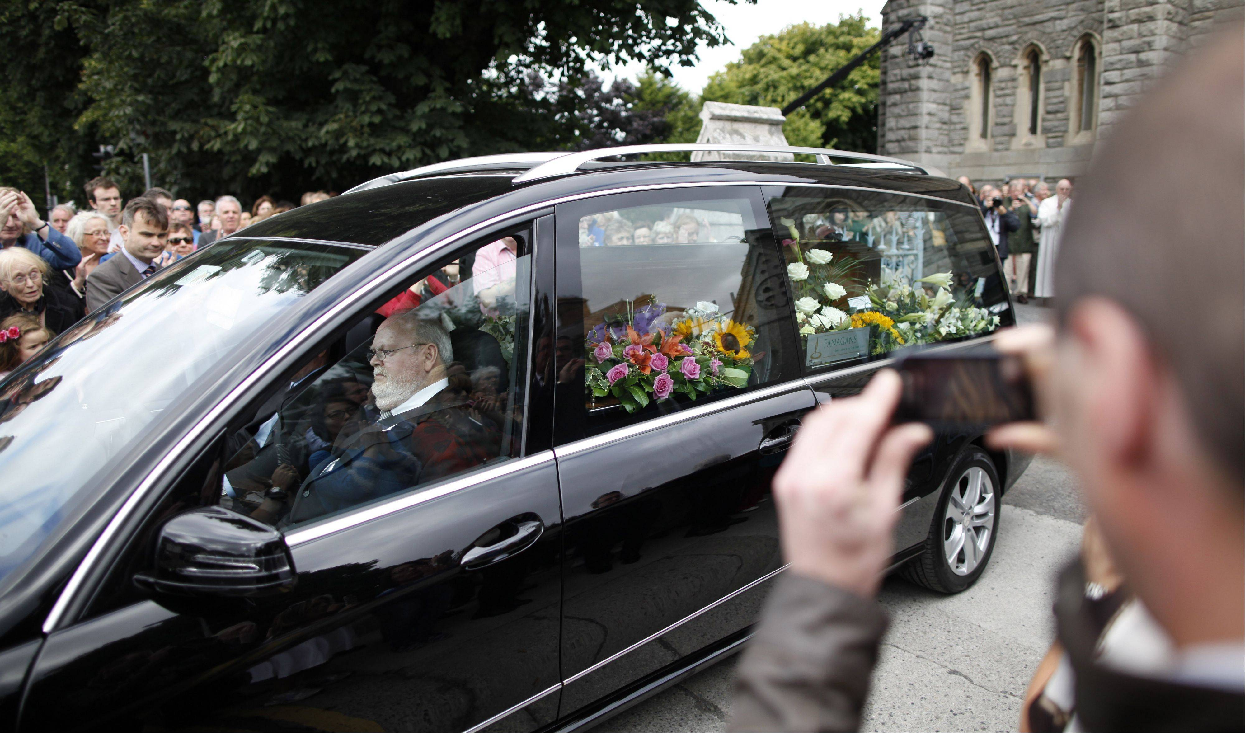 People watch the coffin of Irish poet Seamus Heaney leave the Church of the Sacred Heart in Donnybrook, Dublin, Ireland, Monday, Sept. 2, 2013. Heaney who died aged 74, won the 1995 Nobel Prize for Literature �for works of lyrical beauty and ethical depth, which exalt everyday miracles and the living past�. He was widely considered Ireland�s greatest poet since William Butler Yeats.